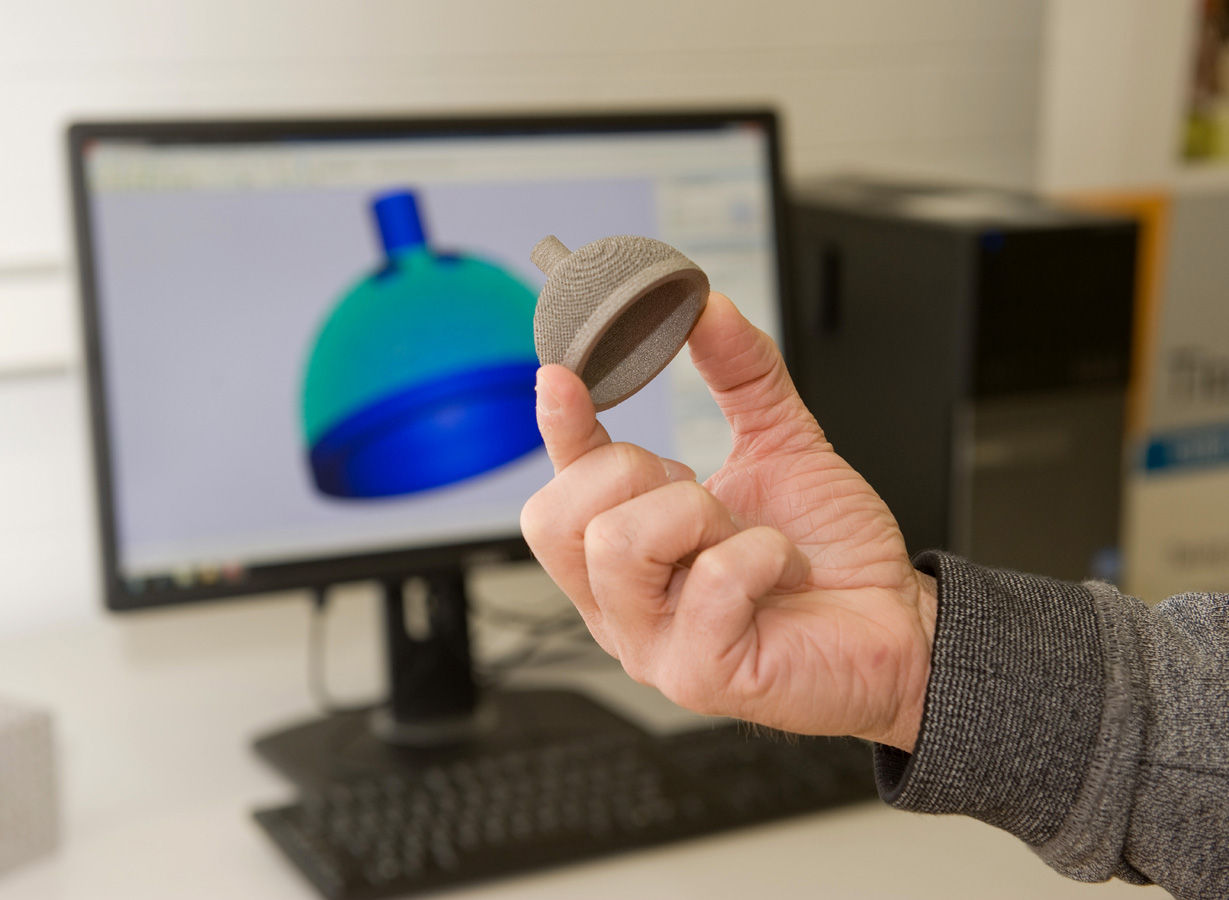 Hand holding titanium #D prinited object in foreground with CAD drawing of the same object displayed on computer screen in background.