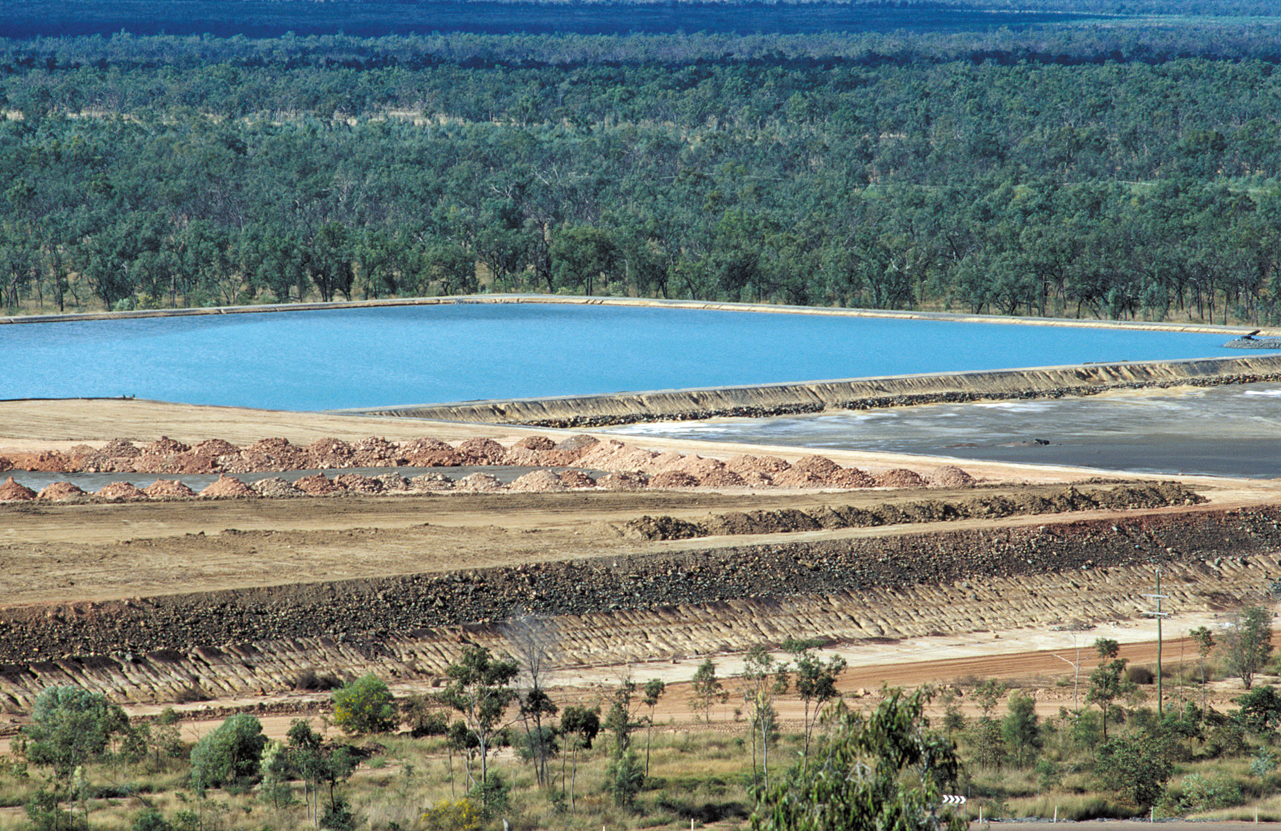 Rural landscape showing copper talings mine and body of water.
