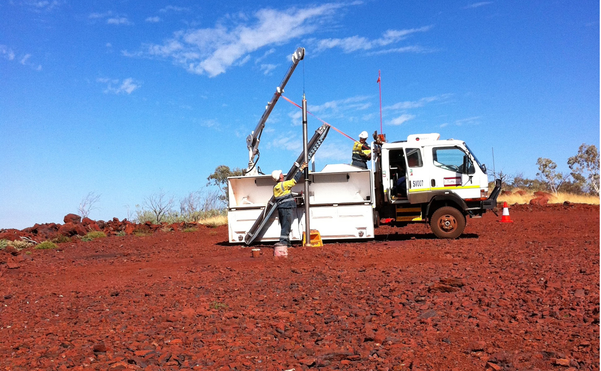 Two workers in a rocky outback field in front of a truck with pulley systems attached to probe sinking into ground