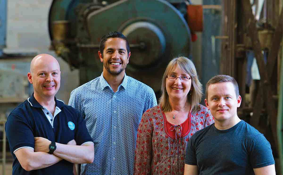 Four members of the sensai team standing in front of industrial machinery
