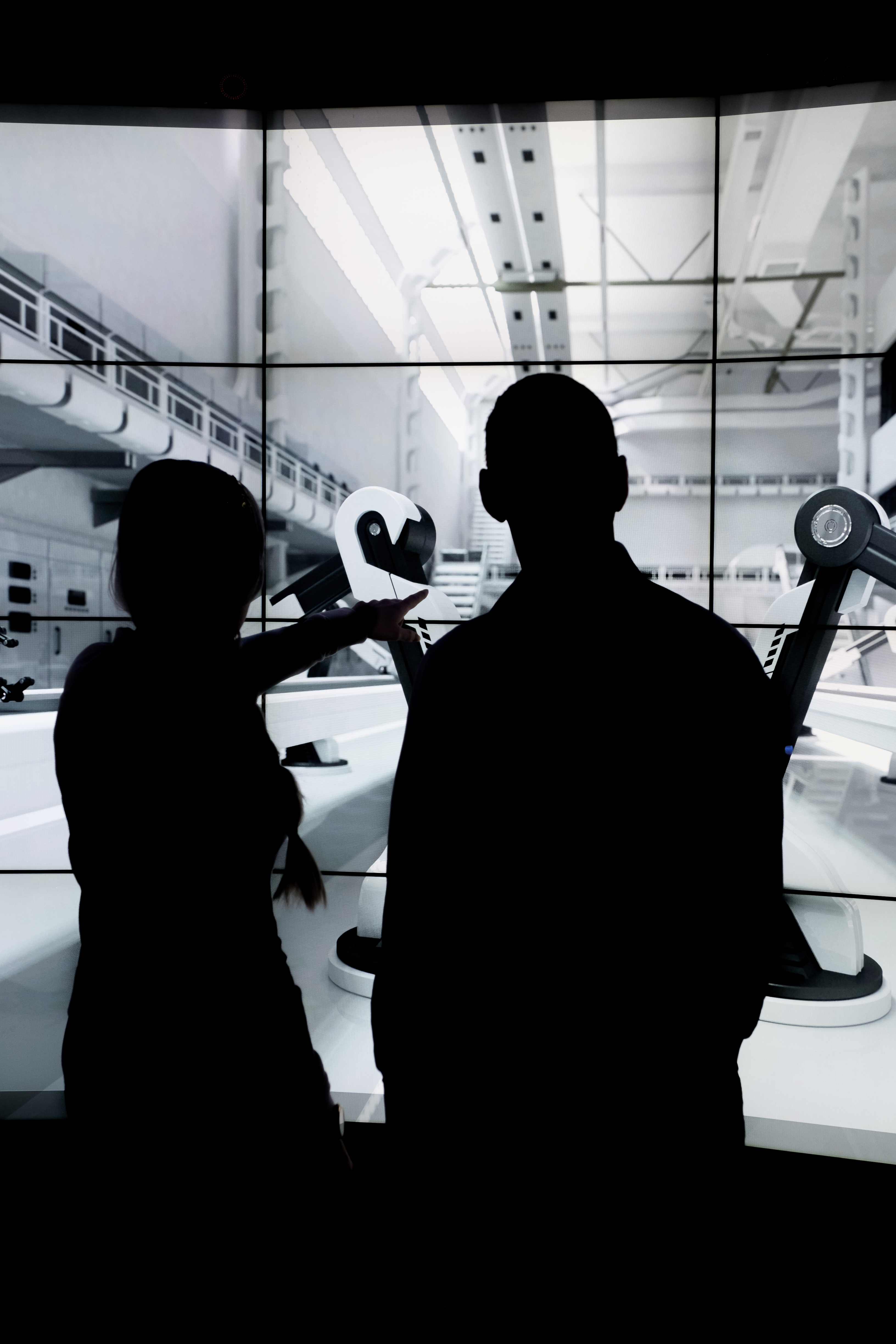 Sillouette of two people infront of screen showing robots in a factory