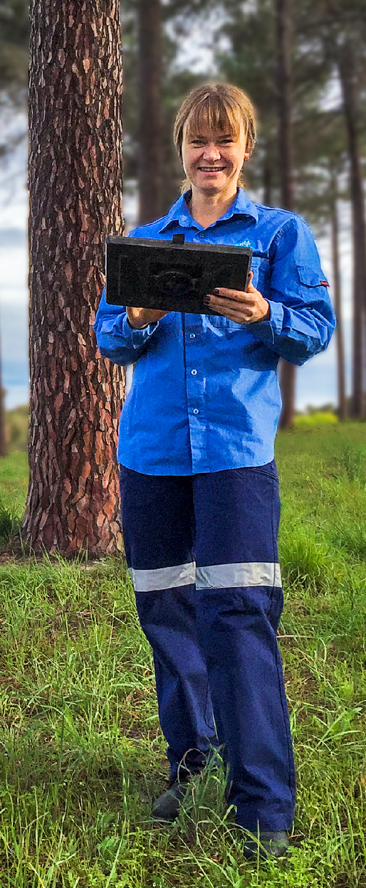 Female geologist standing in a greenfield holding a tablet device