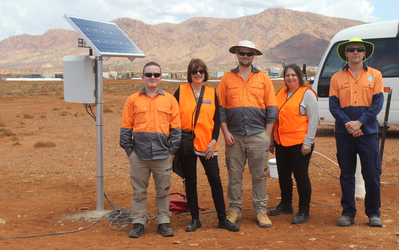 Group of five researcher in high vis clothing stadning against red dirt landscape