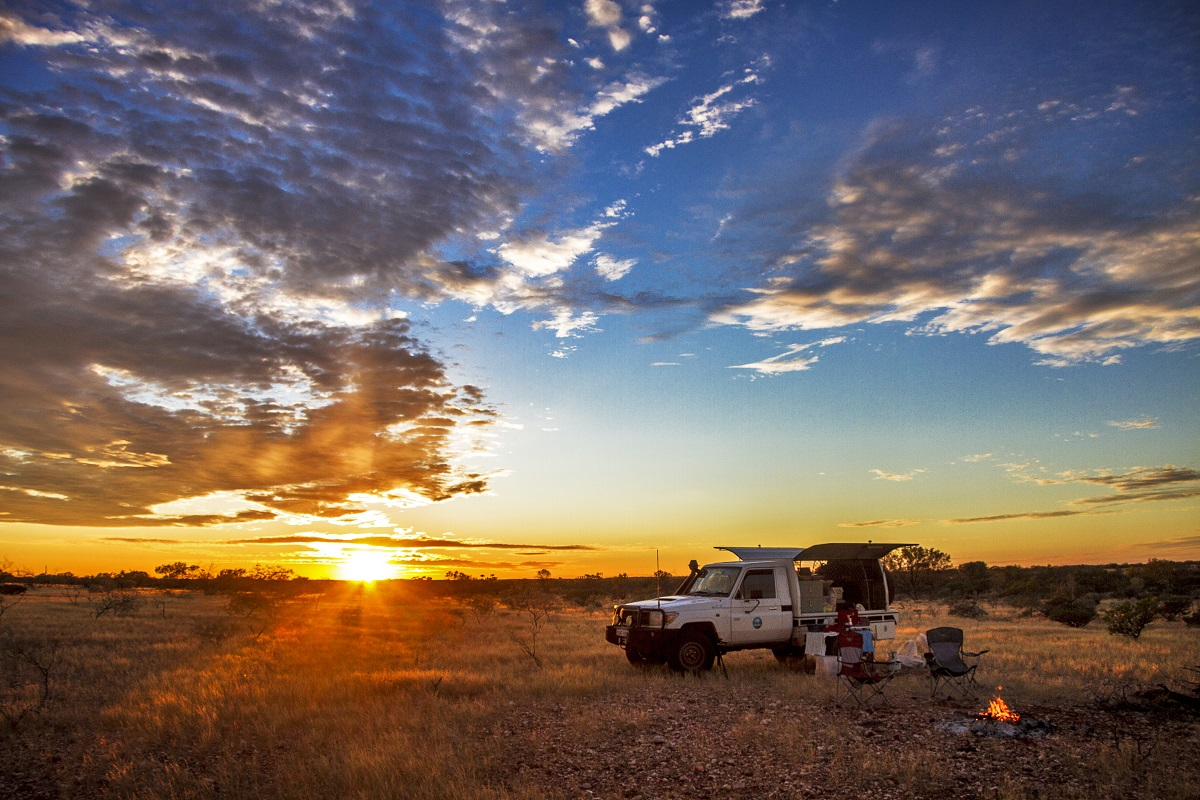 Four wheel drive car parked in outback landscape at sunset