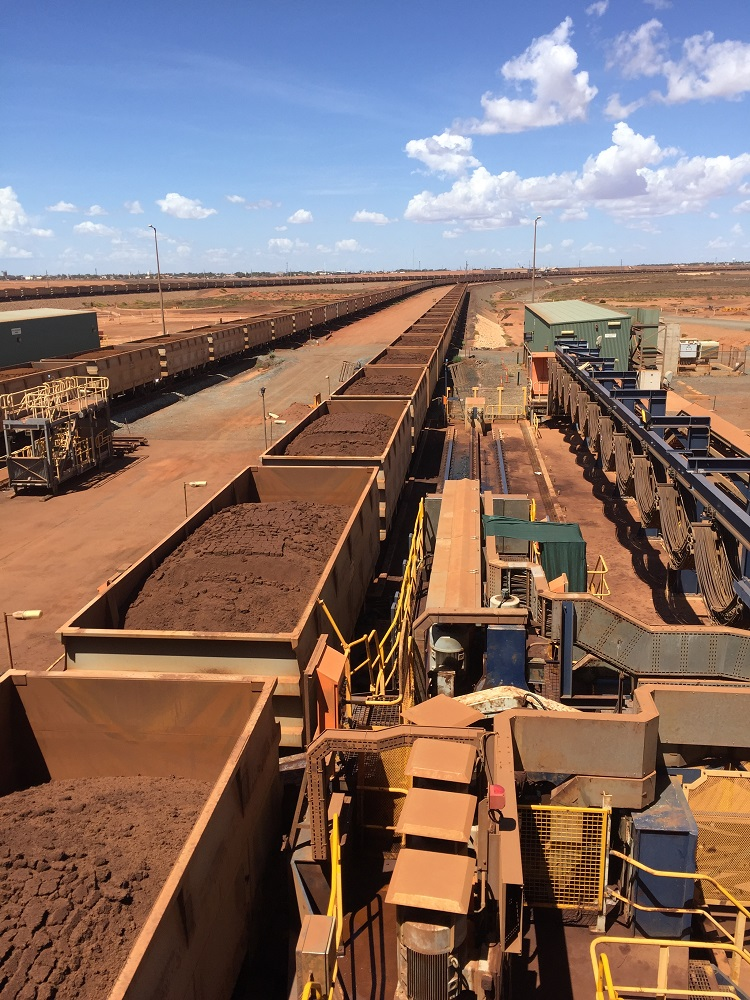 Long chain of open rail carriages filled with rust-coloured iron-ore rock winding into outback landscape