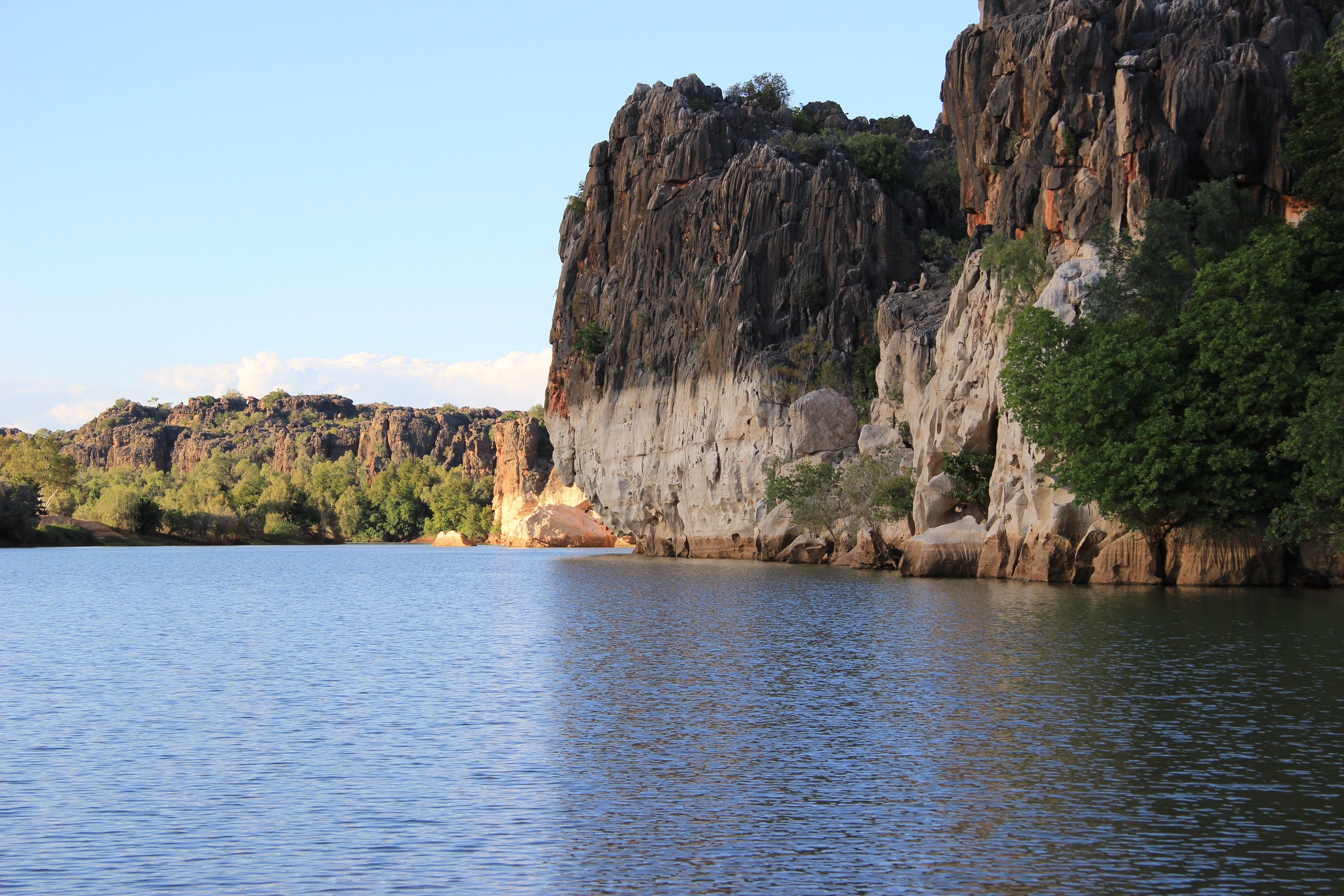 Geikie Gorge showing water in the foreground and steep cliffs bordering the gorge to the right in the background.
