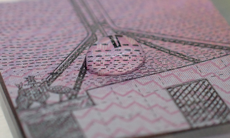 A droplet of liquid forming a circular mound in the middle of a small sqaure of cut Australian five dollar banknote.
