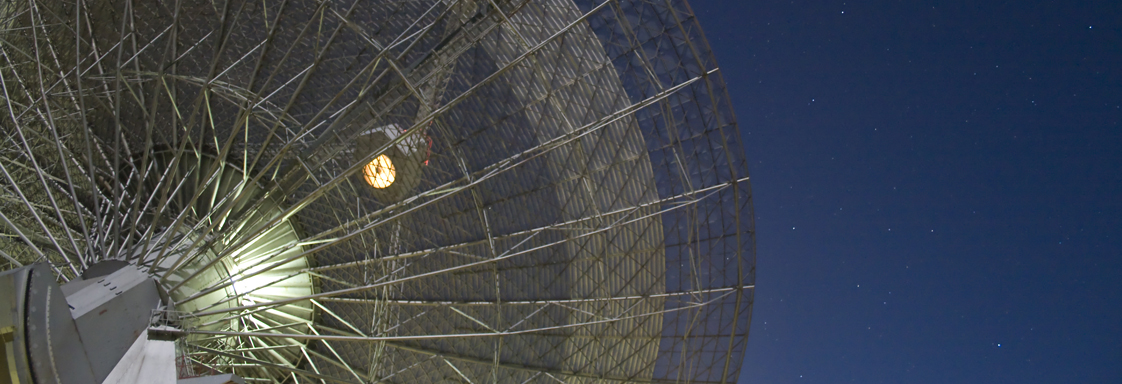 Wire mesh of a radio telescope dish with a starry sky in the background.