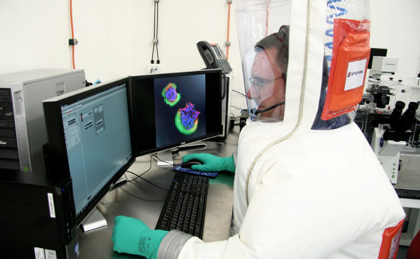 Man in protective suit and helmet looking at two monitors