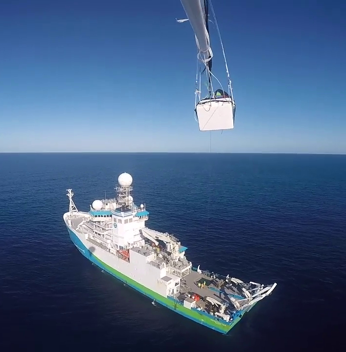 A piece of scientific equipment at the top of the image and below is a full view of the research vessel, Investigator, on the ocean.