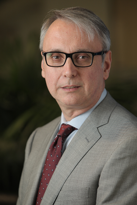 Dr Manuel Blanco, wearing a grey suit and black framed glasses.