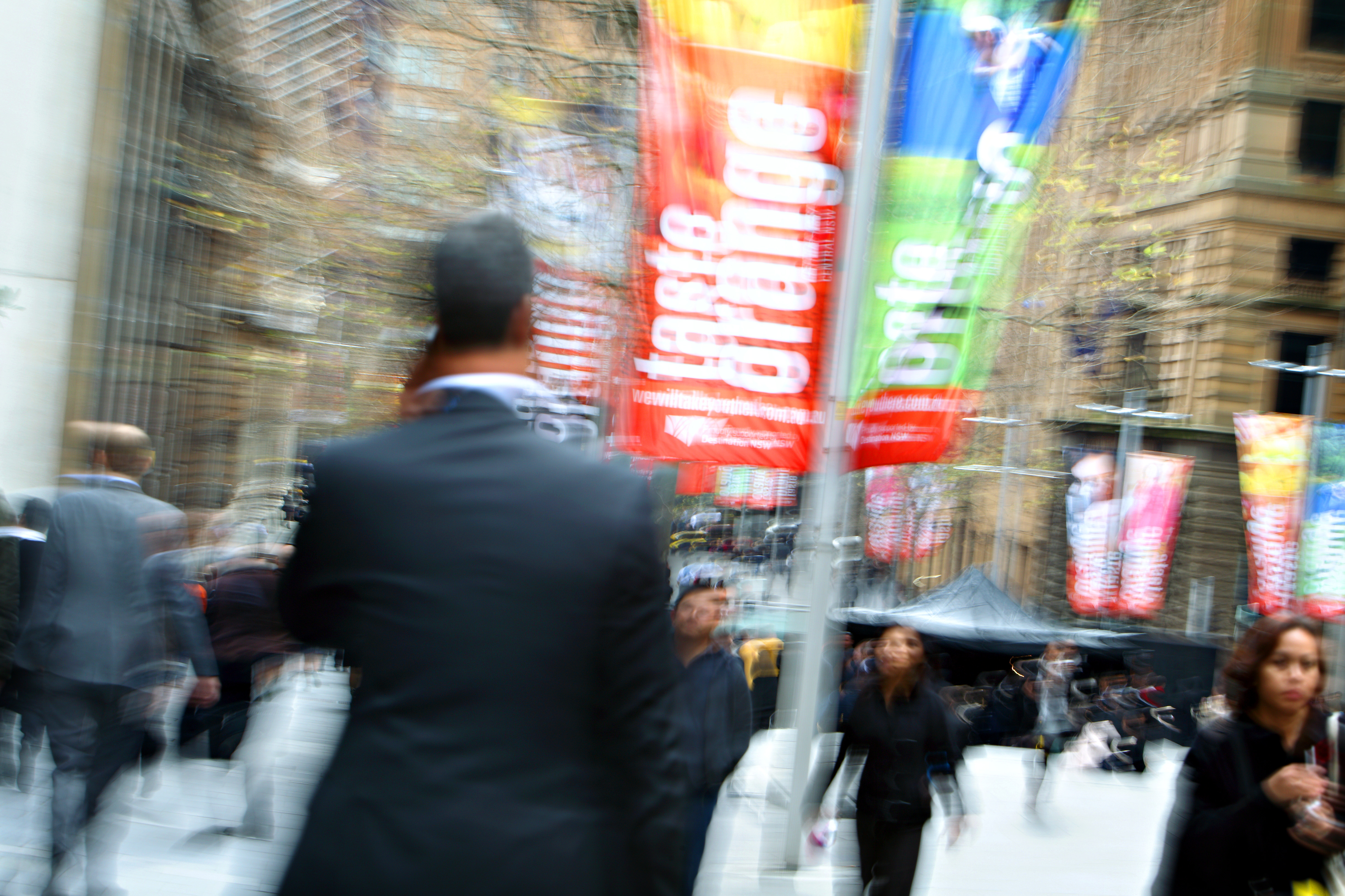A busy pedestrian street, blurred by motion.