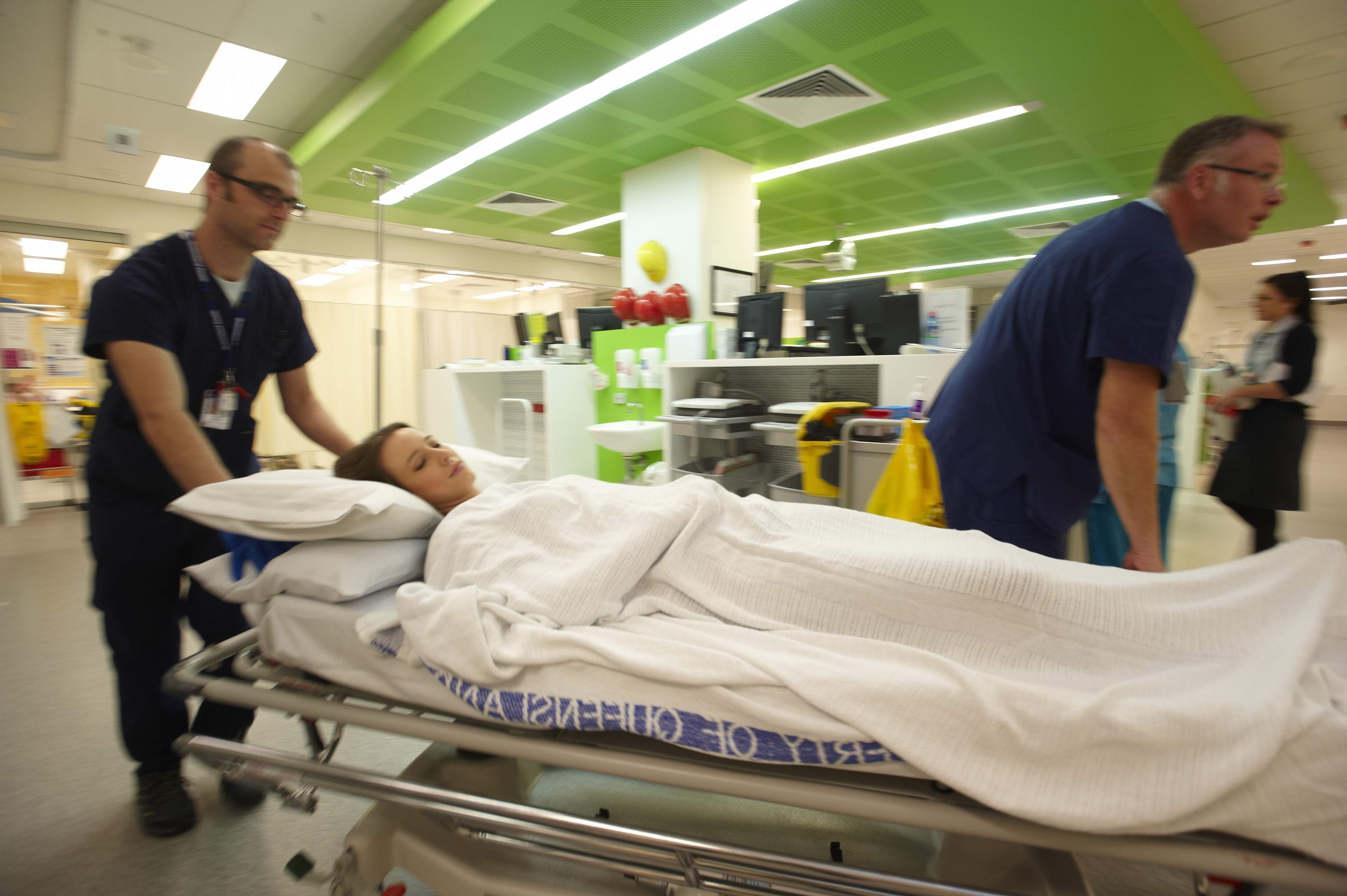 A young patient arriving in hospital emergency on a stretcher with two medical staff attending.