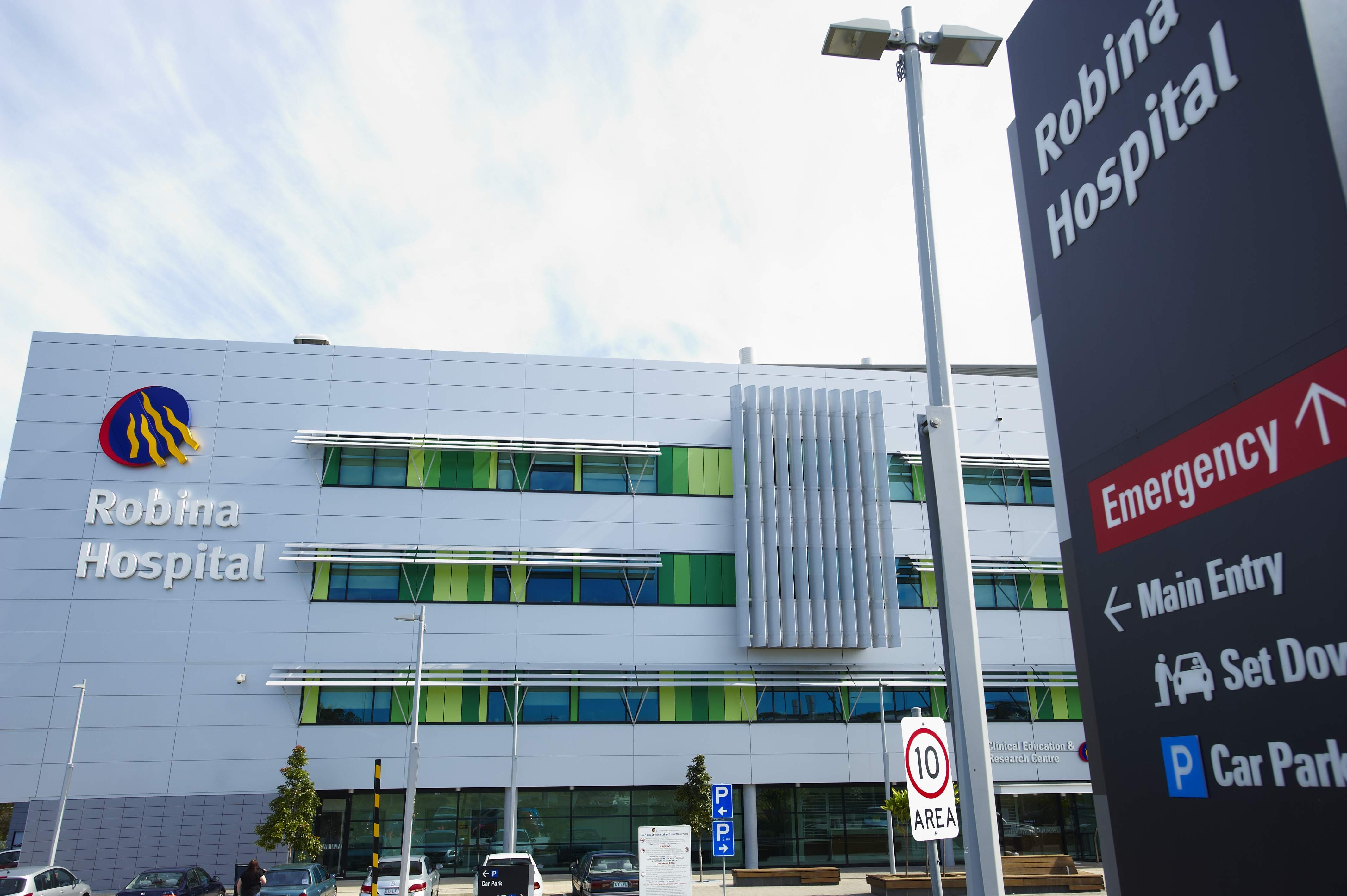 The outside of a multi storey building with signage showing Robina Hospital and direction signs