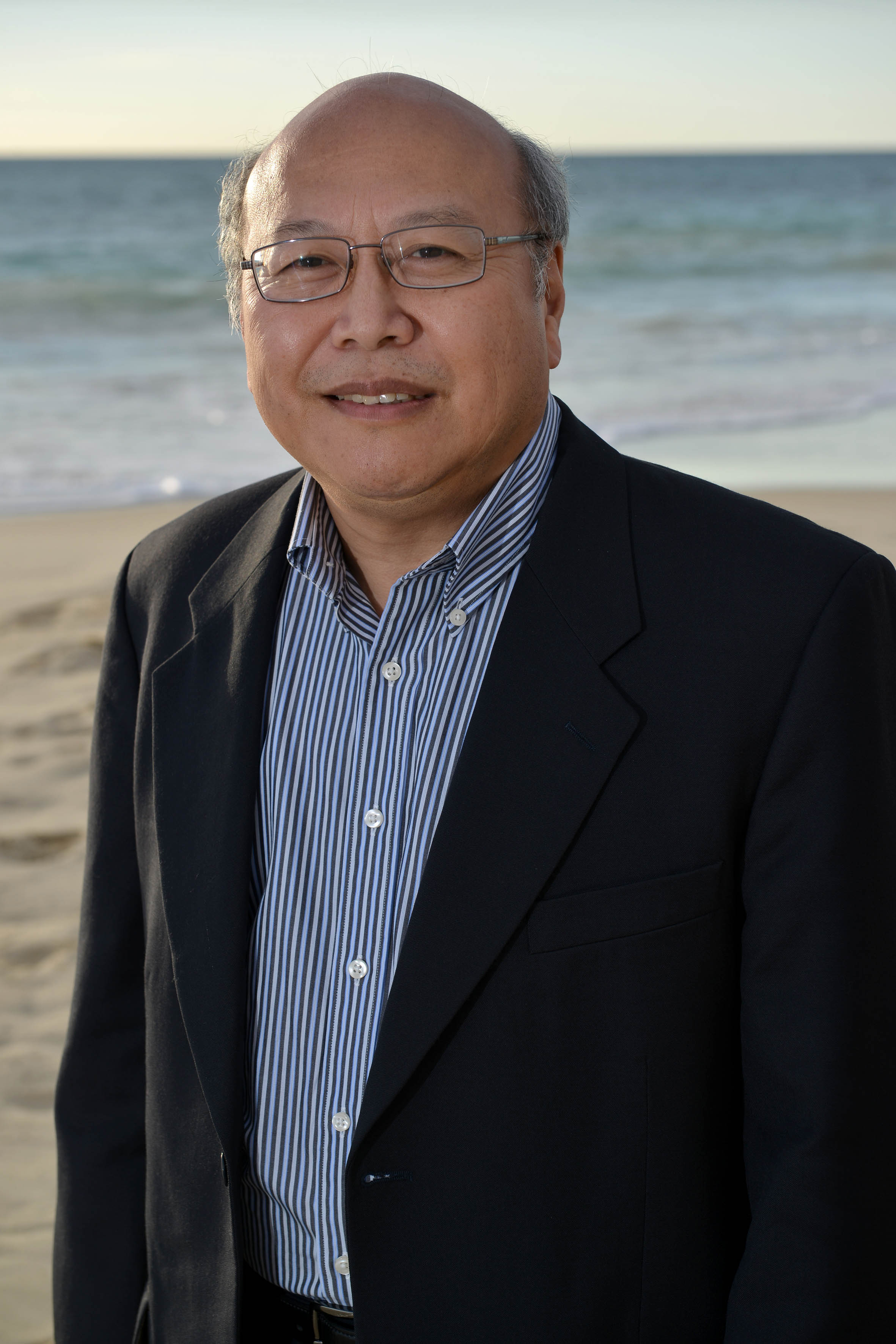 Portrait photo of Dr Ken Lee with beach and ocean as the backdrop.
