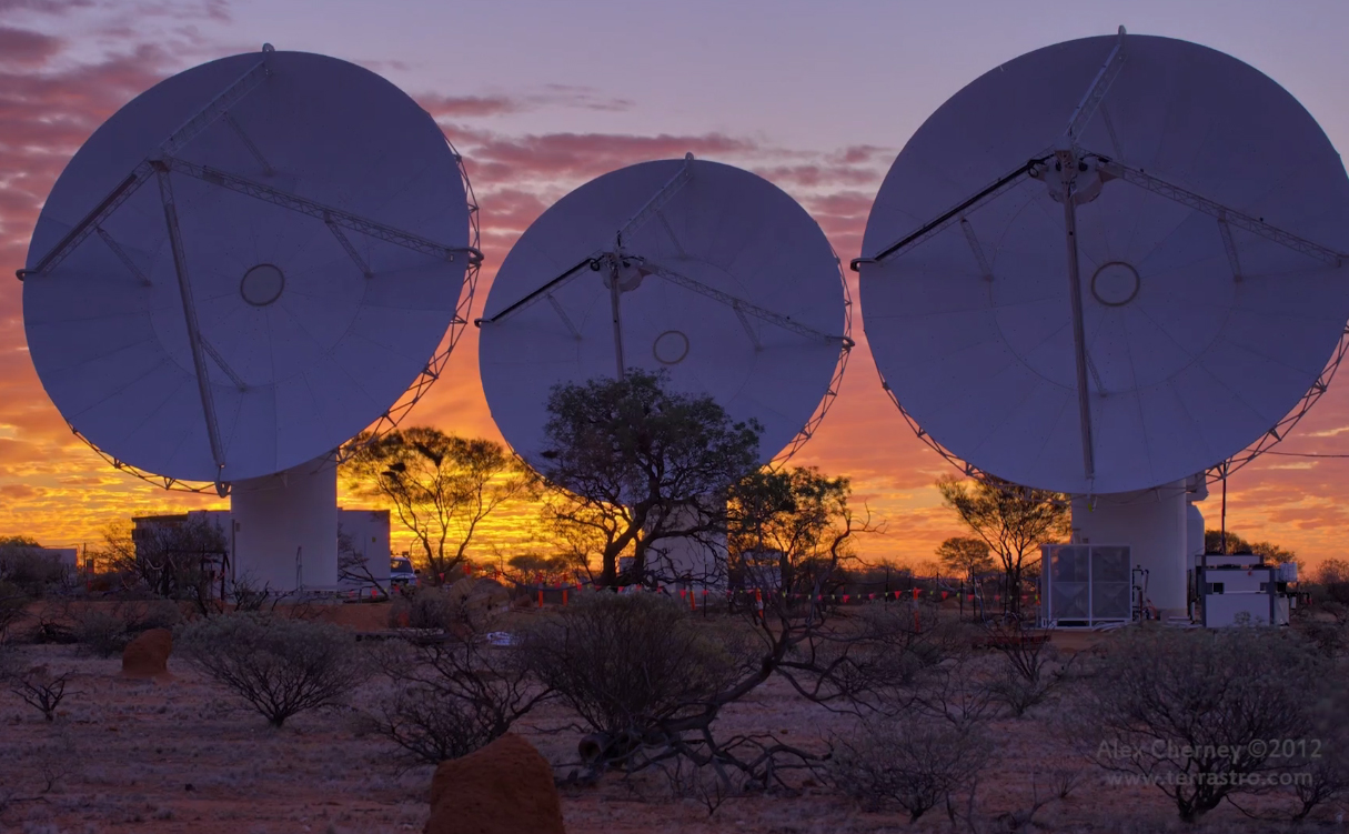 Three radio telescopes at dawn.