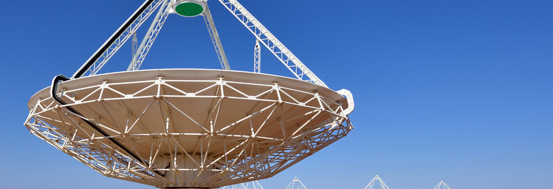 Close up of a radio astornomy telescope with several in the distance