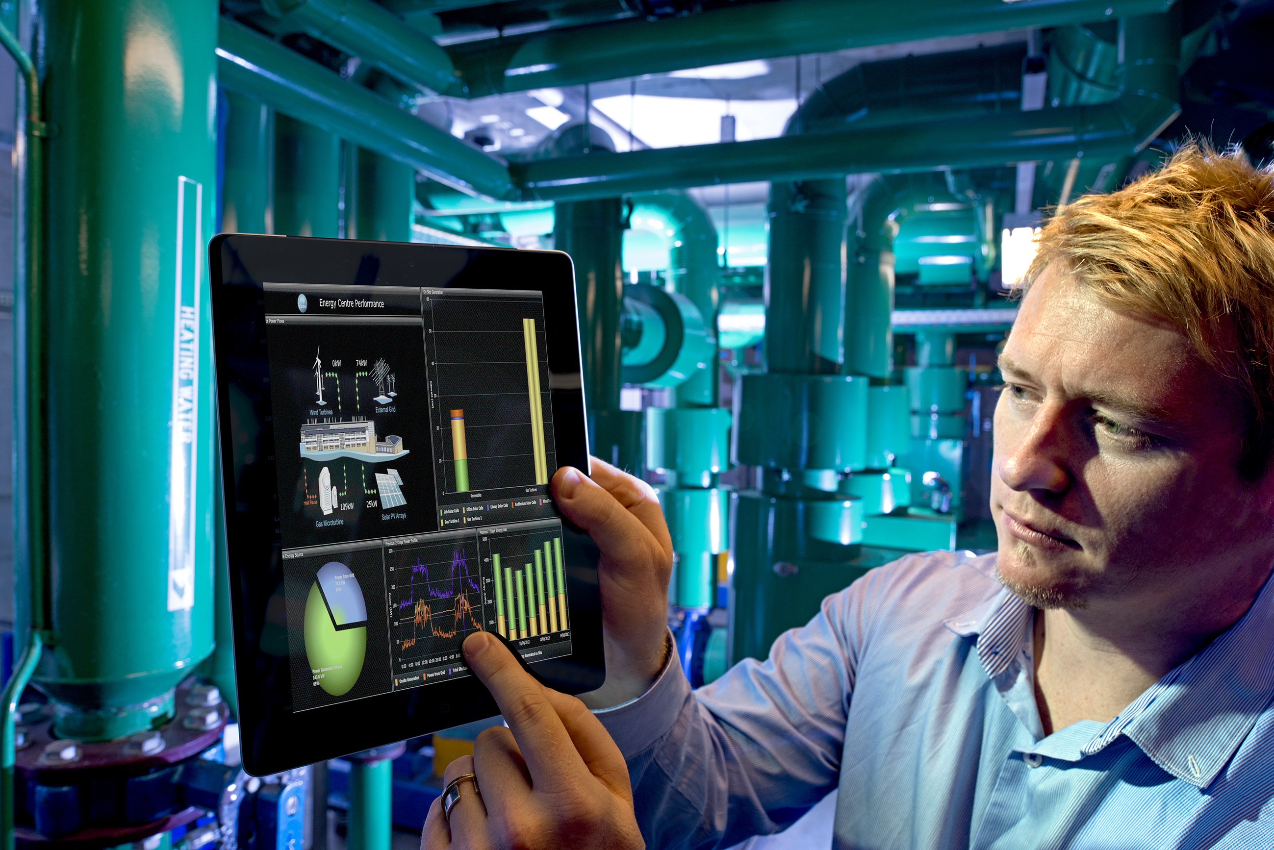 A man interacts with a tablet interface in an energy facility.