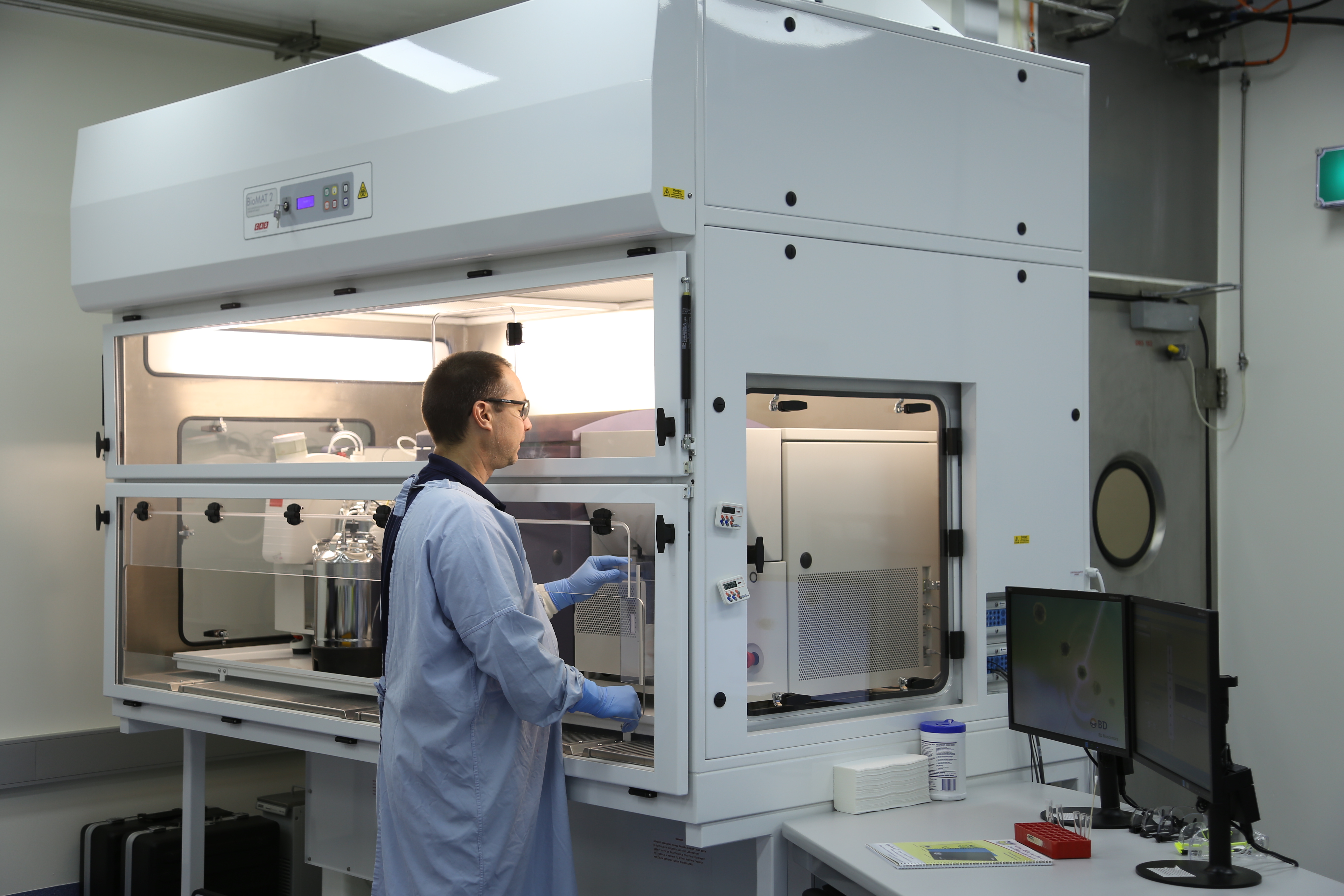 Matt Bruce, a CSIRO immunology researcher, loads a sample into the cell sorter to isolate virus fighting cells.