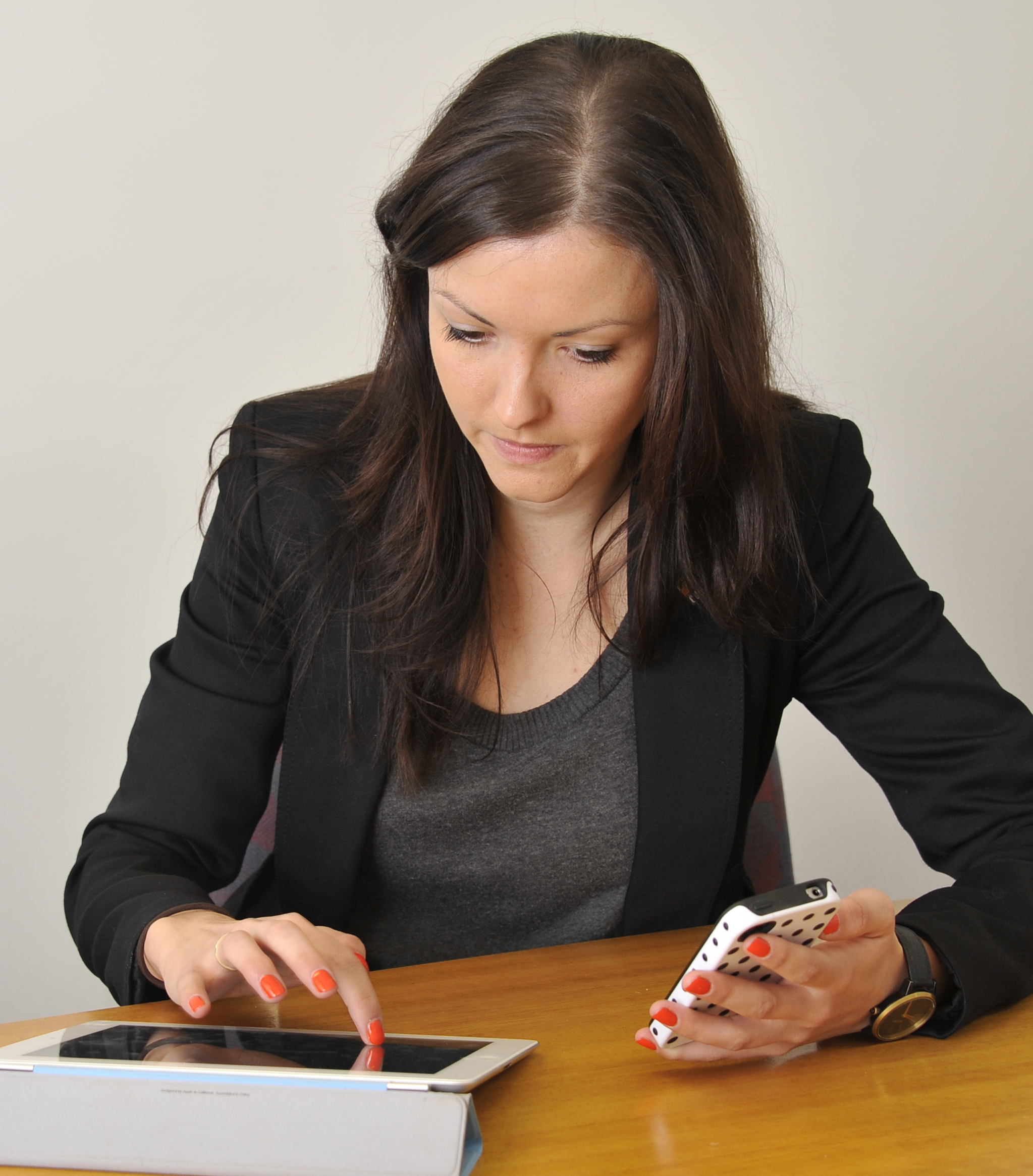 Woman sitting at desk using a tablet and smartphone