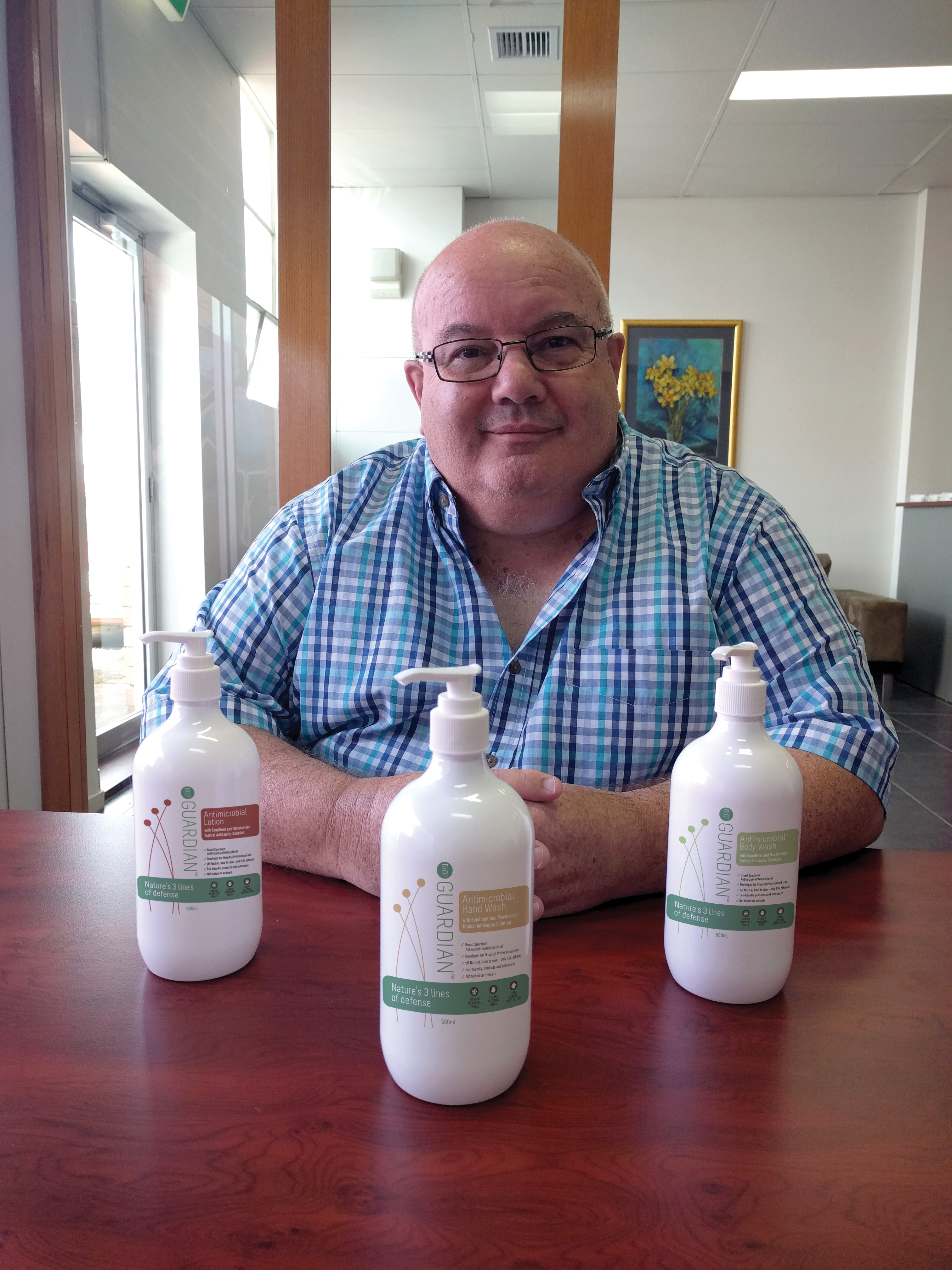 Frank Palermo sitting at a table behind bottles of Bio3 Guardian.