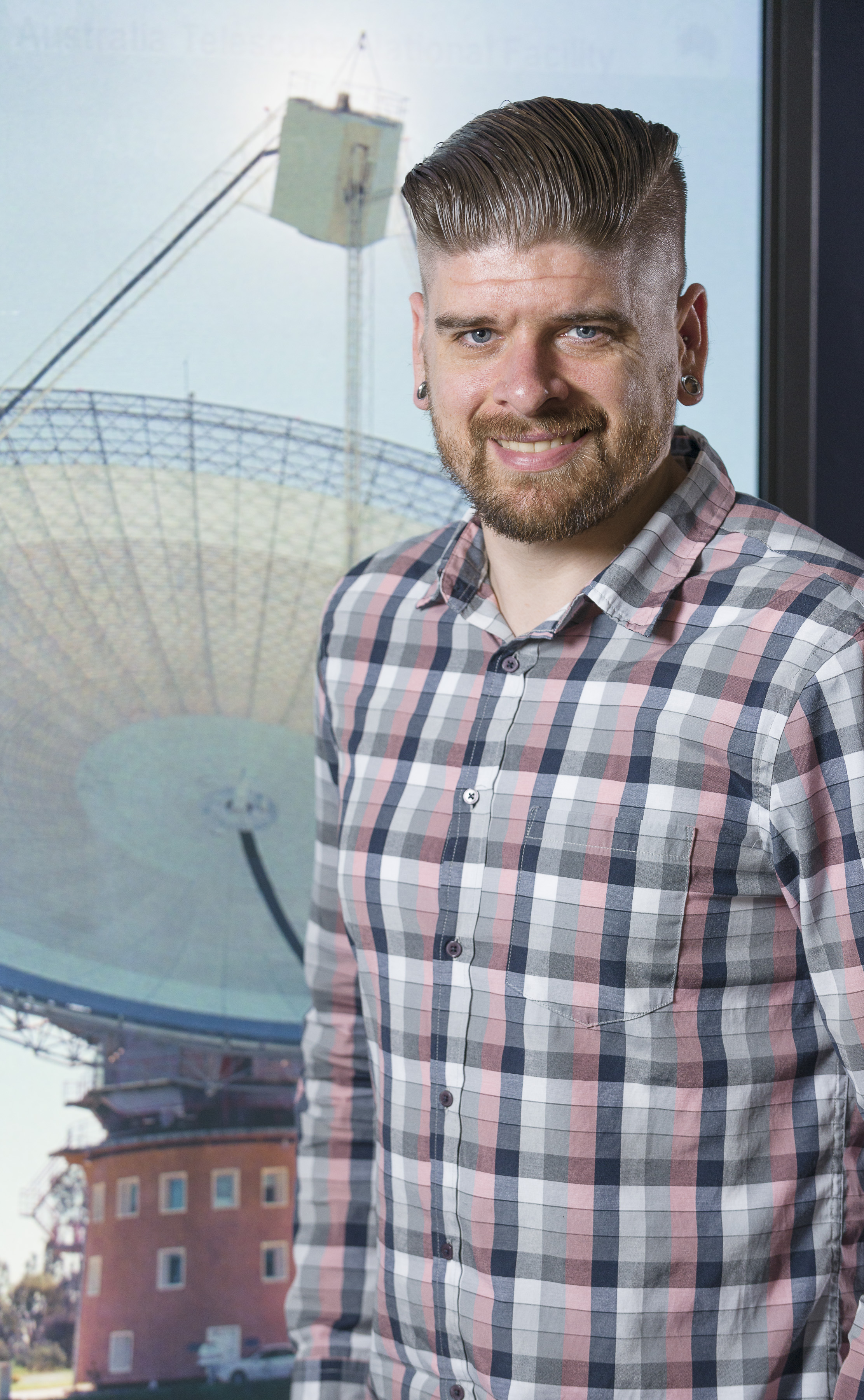 Dr Ryan Shannon standing in front of a radio telescope.