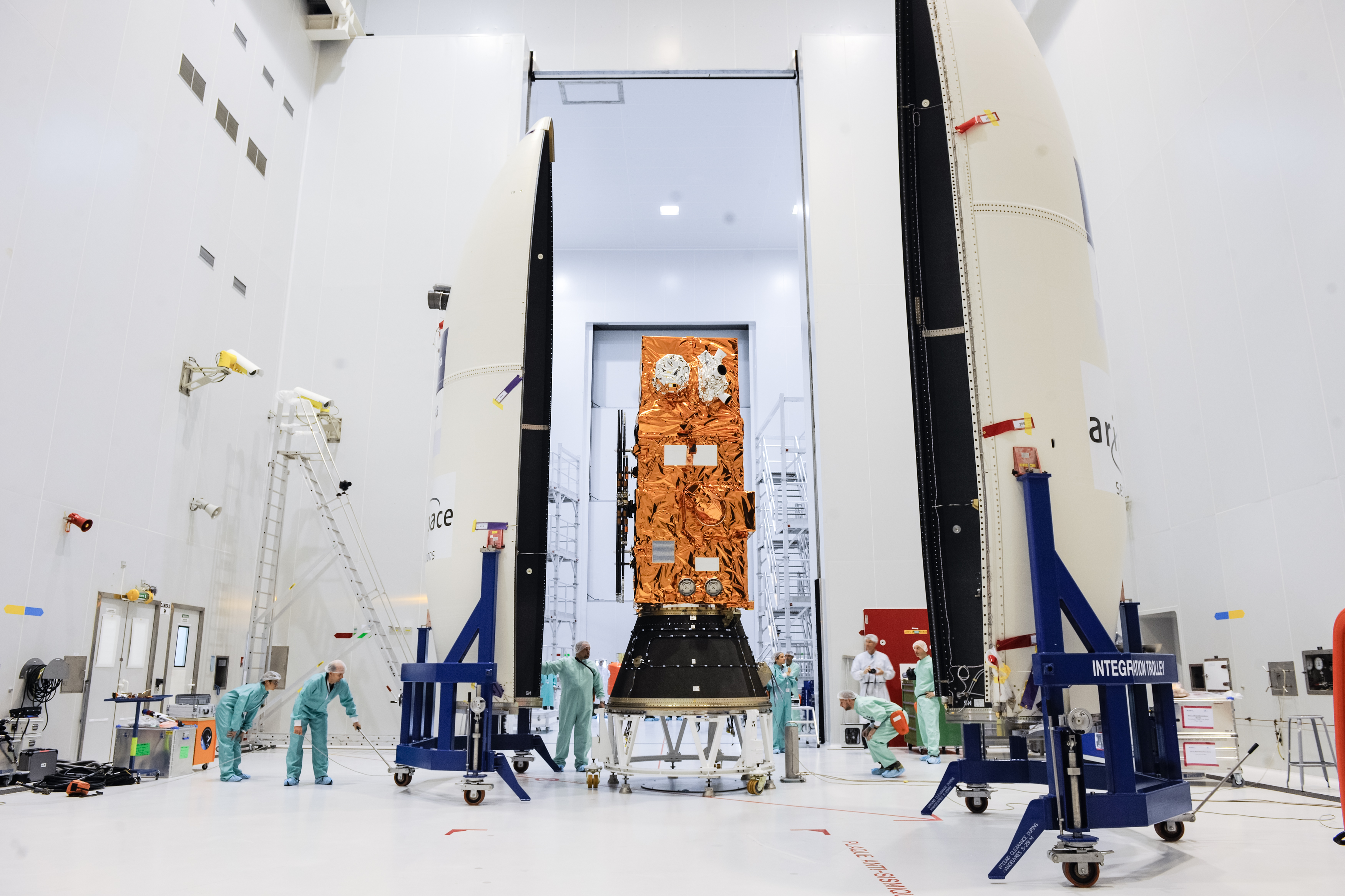Sentinel-2A satellite being prepared for launch in a laboratory hanger by people in protective overalls and head coverings.