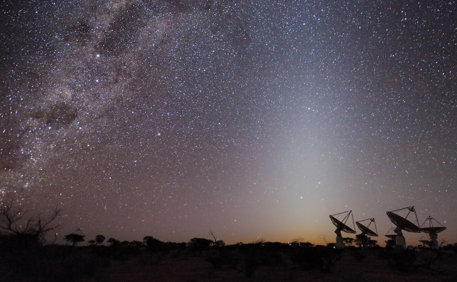 View of a starry night sky with radio telescopes in the background.