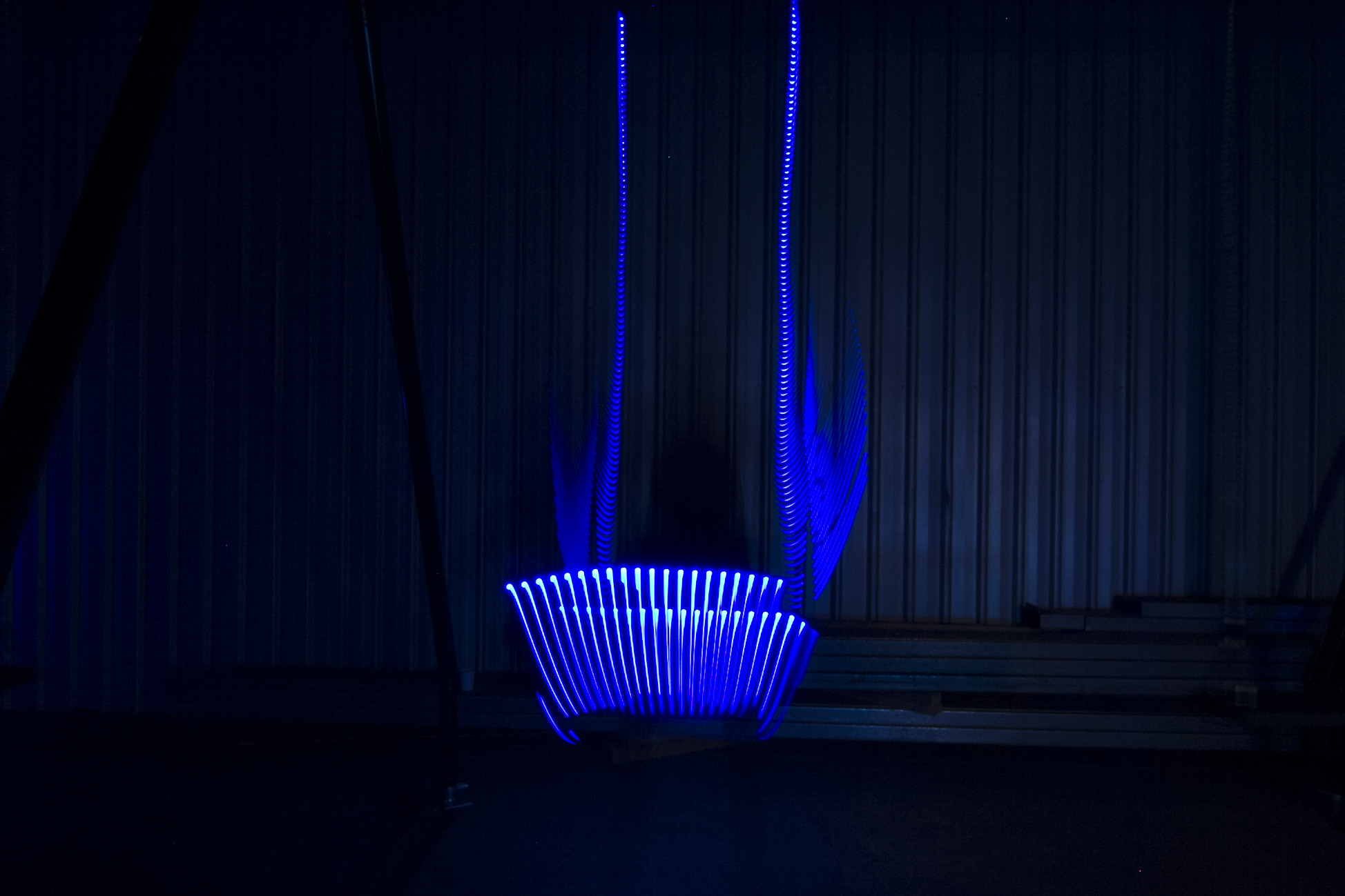 One seat of the Infinity swing glowing in blue light.