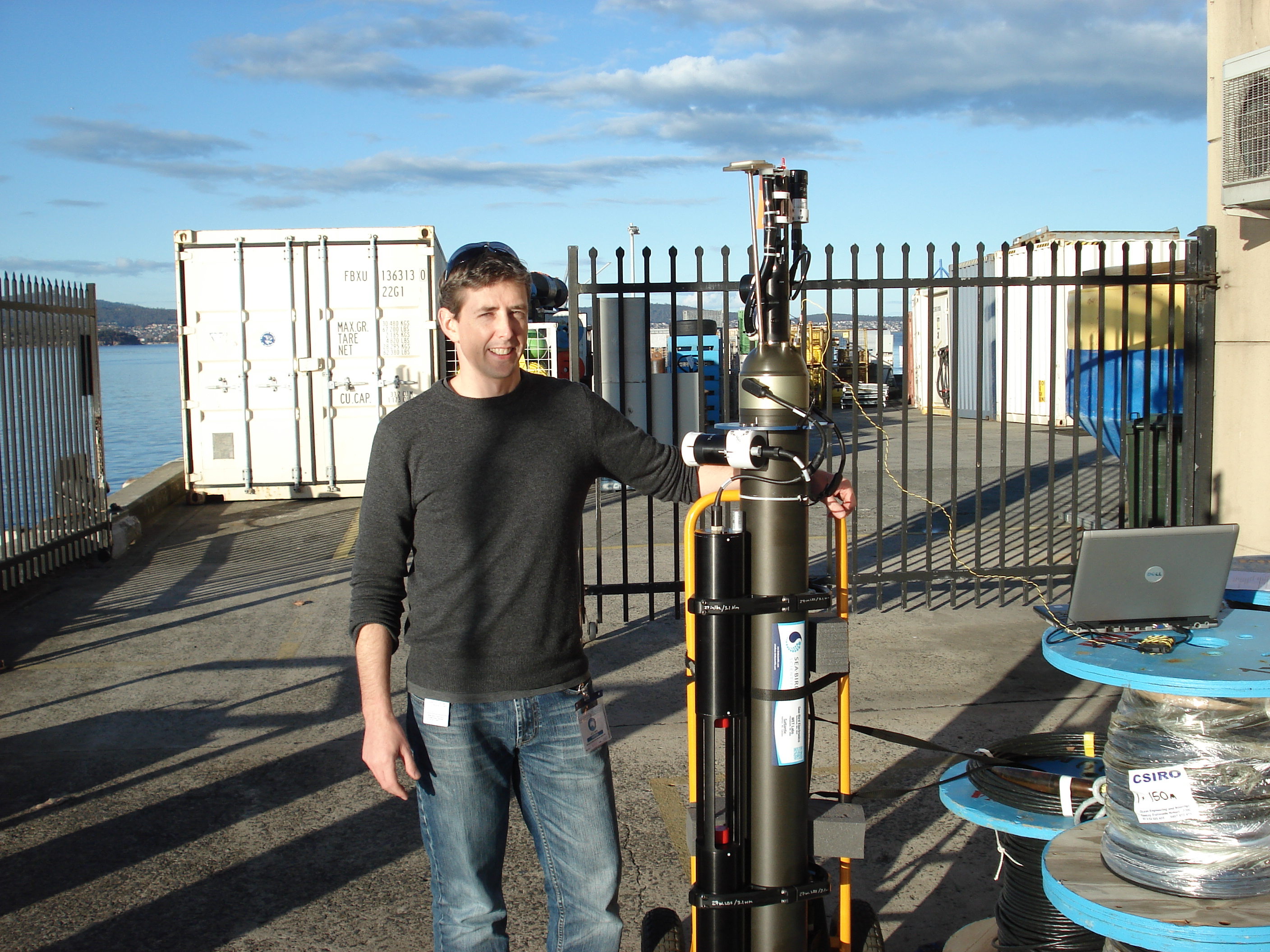 Nick Hardman-Mountford standing on a warf, resting arm on a BioArgo robotic float.