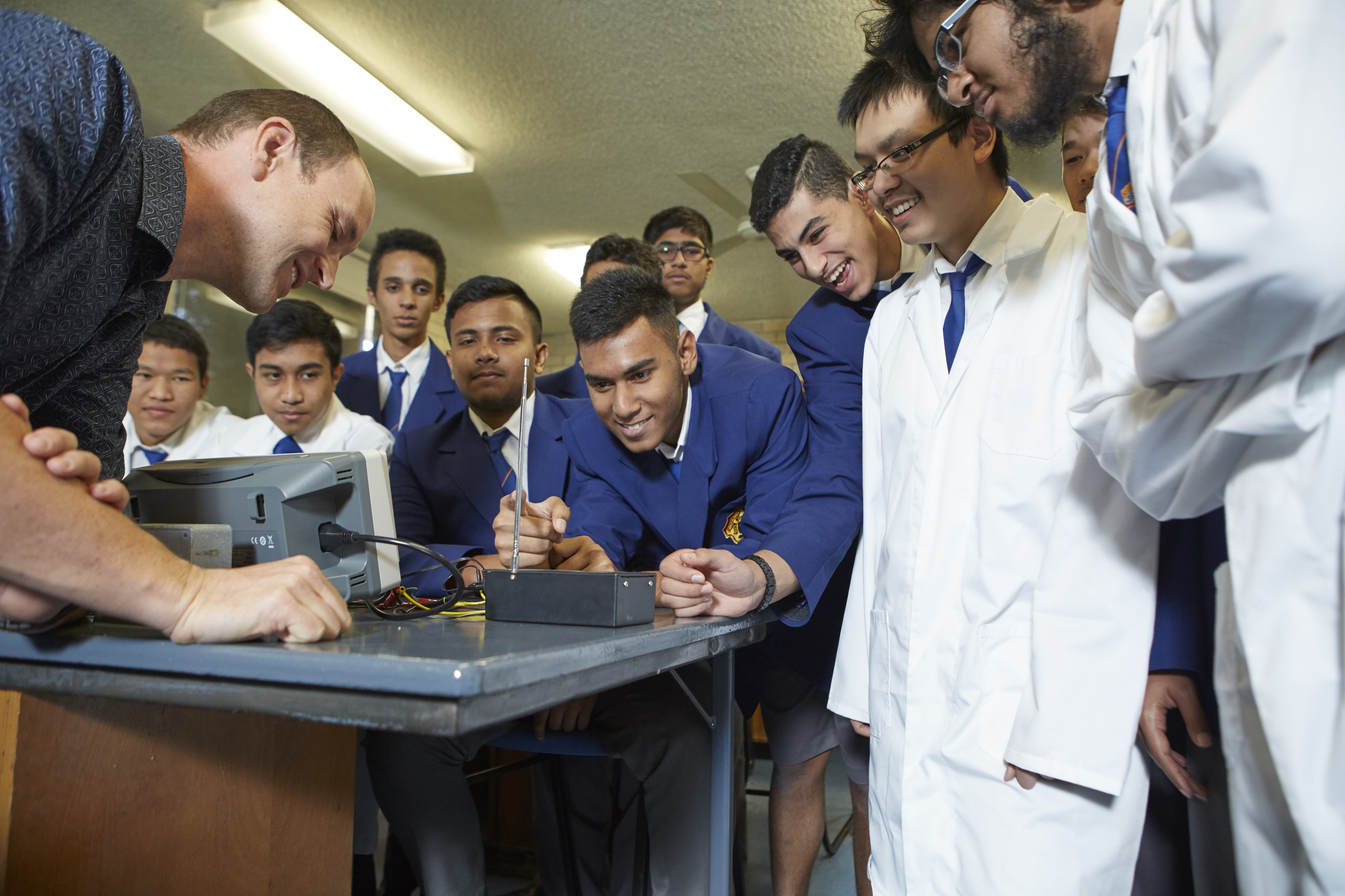 Teacher and students standing around a lab desk watching an experiment.
