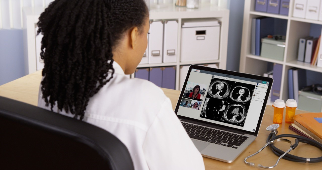 Doctor sitting in front of laptop showing Data61's Coviu audio-video platform.
