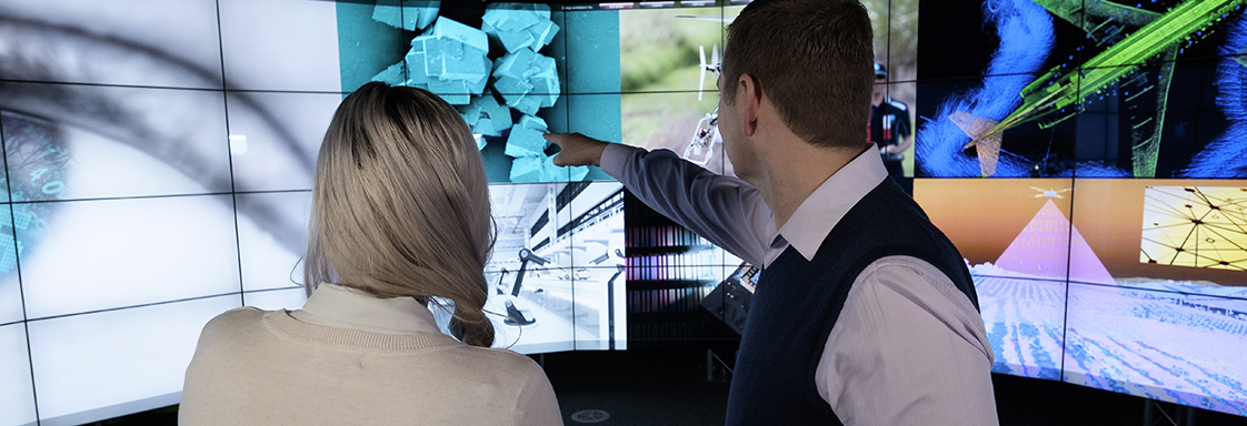 Two people looking at a wall of electronic screens.