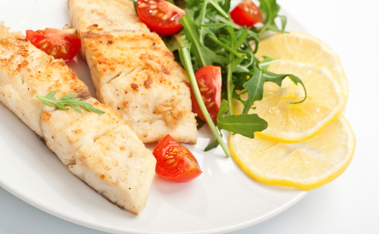 Grilled fish, salad leaves, sliced tomato and lemon on a white plate.