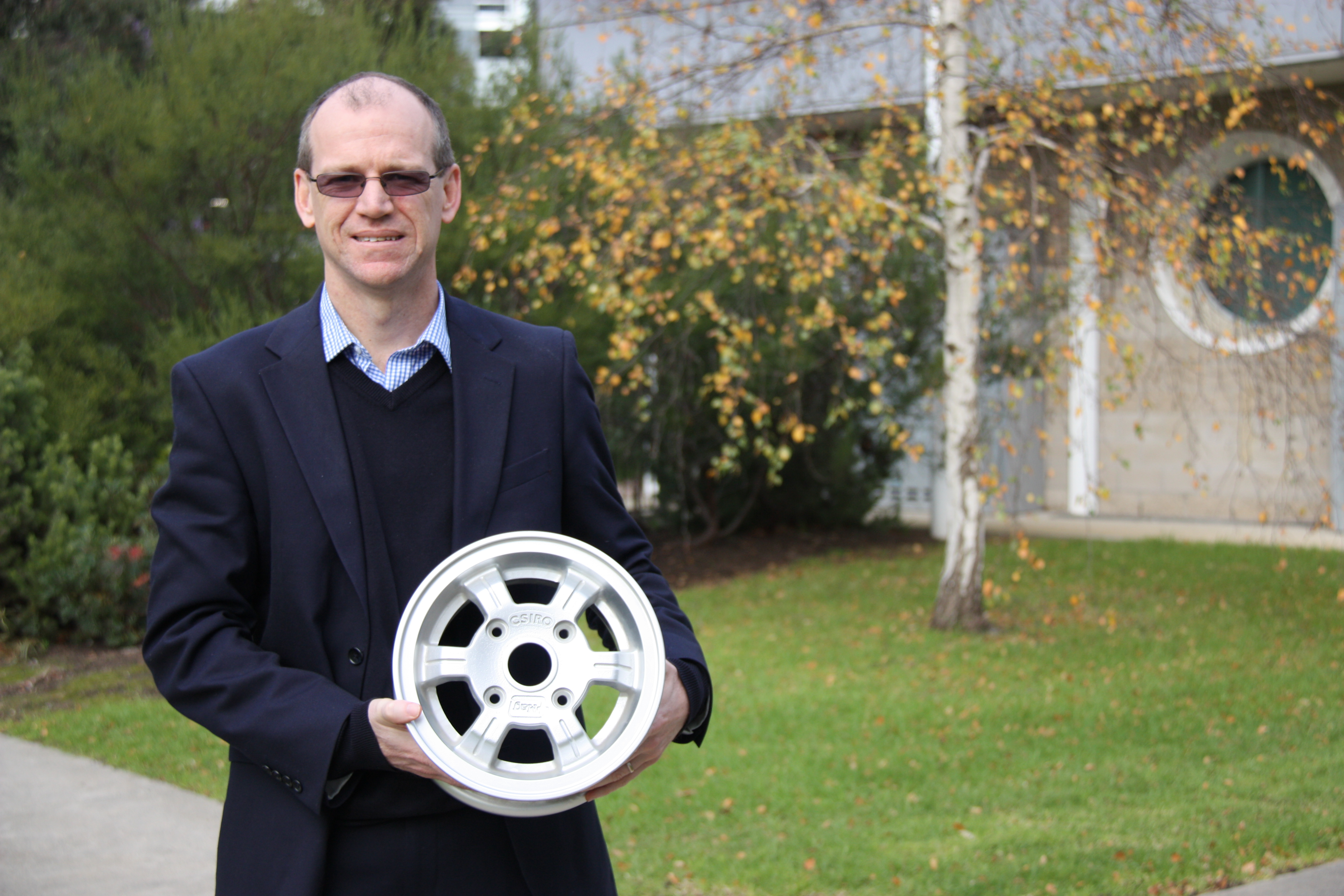 Dr Mark Cooksey holding a magnesium metal car wheel rim.