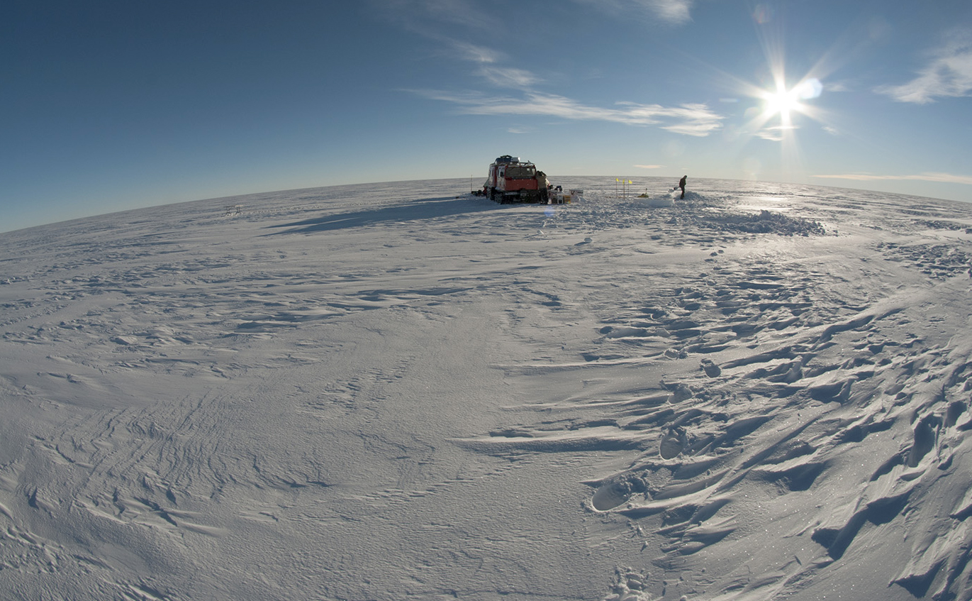 Snowy landscape with ice core drilling camp in the background.