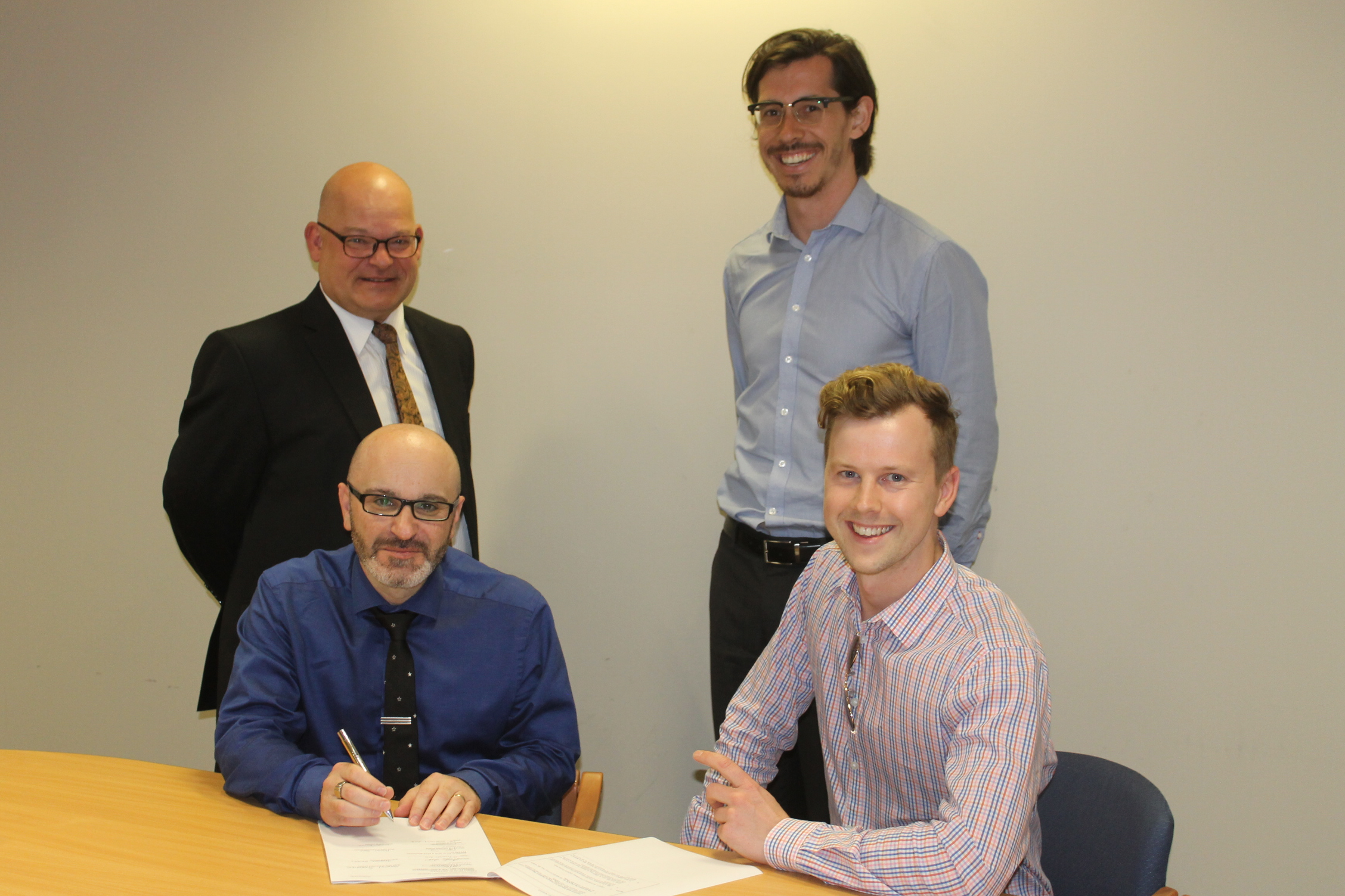 CSIRO's Andrew Stammer and Marcus Zipper signing the agreement with Byron Scaf and Daniel Pikler from Stile Education.