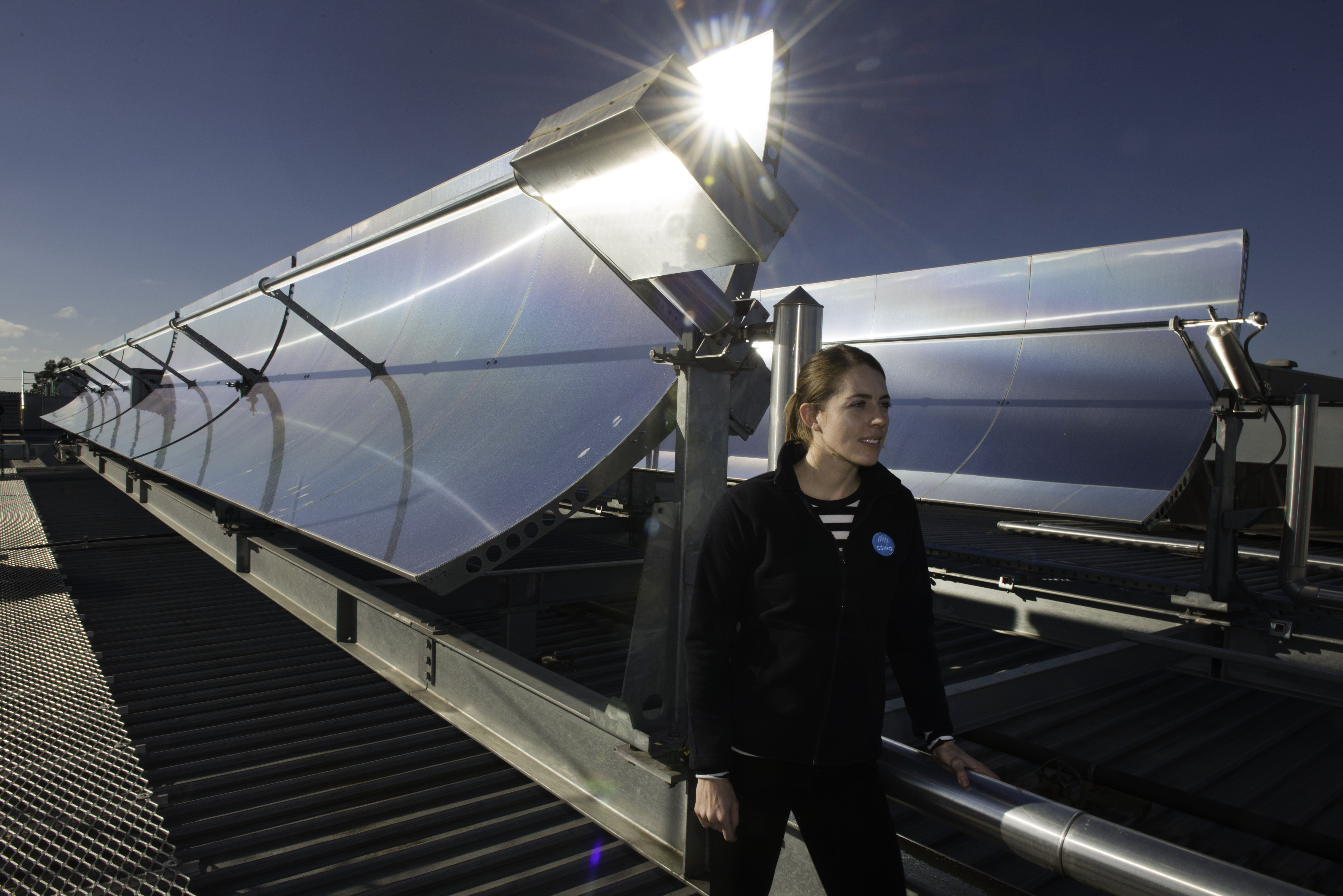 A woman stands in front of rooftop concentrating solar thermal collectors