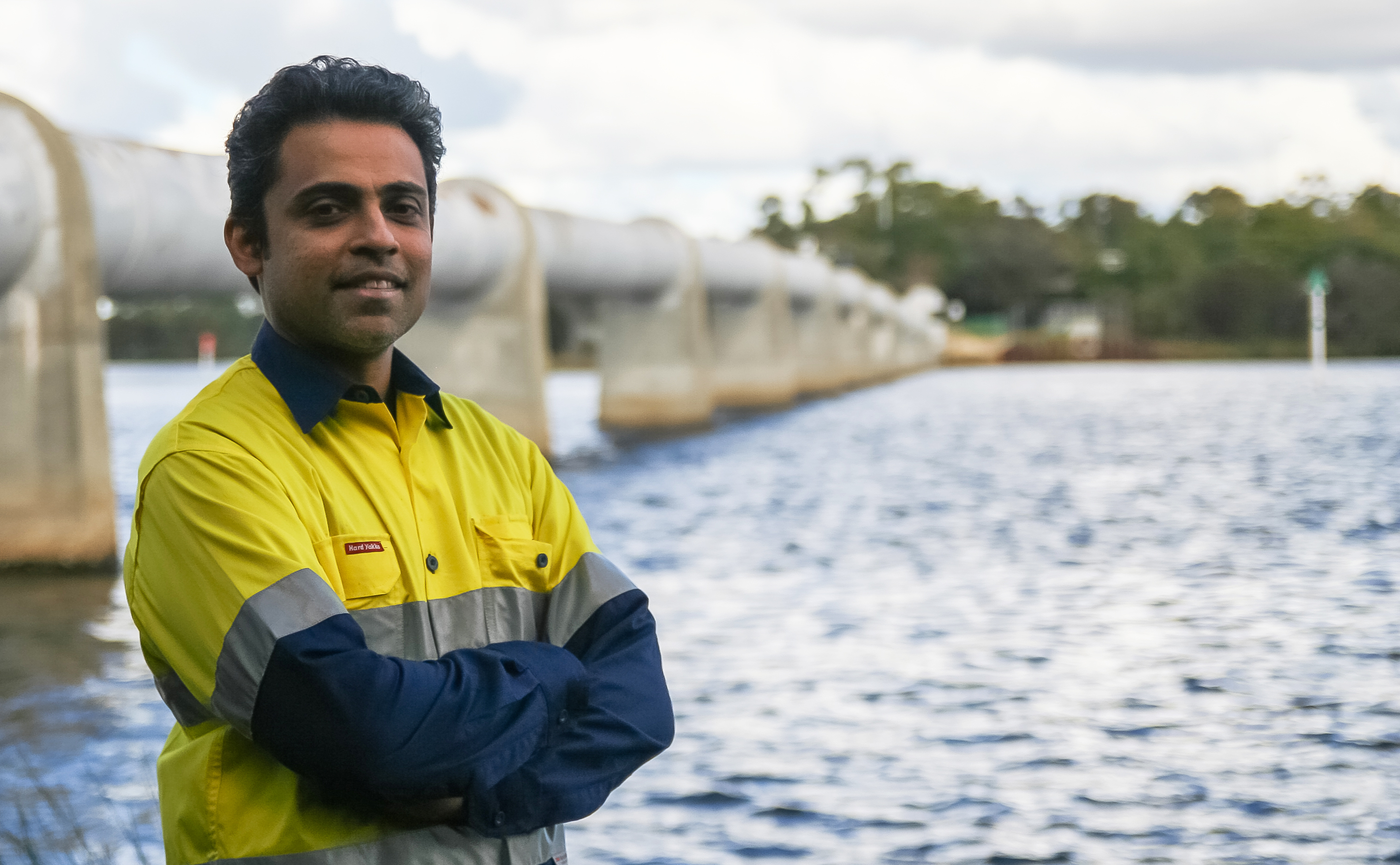 Man in high vis clothes standing next to a body of water with large pipeline running through the background.