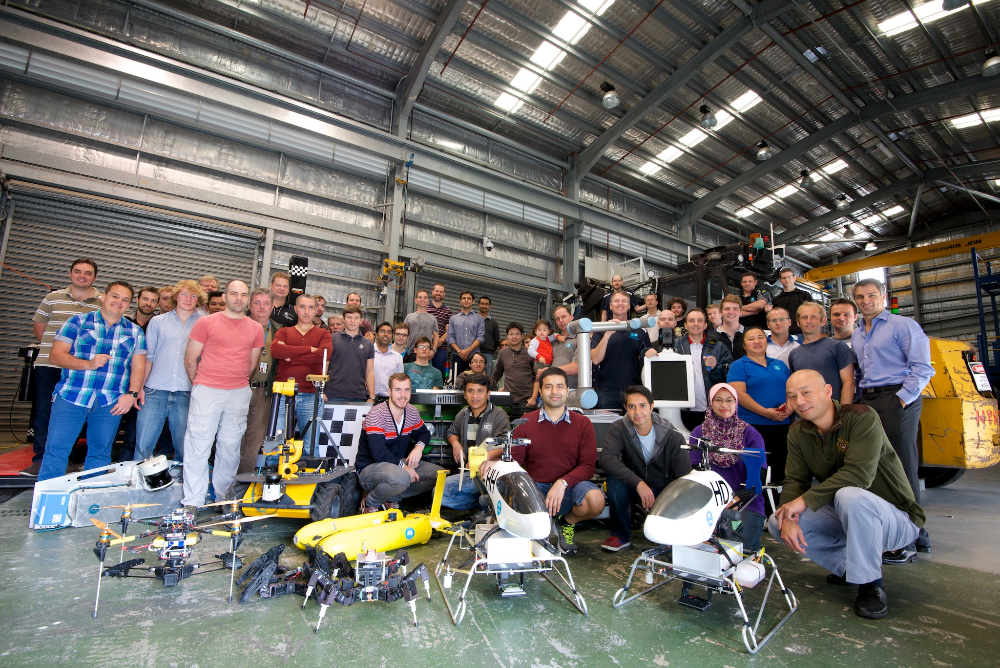 Group of researchers standing behind a variety of robots developed with CSIRO technology.