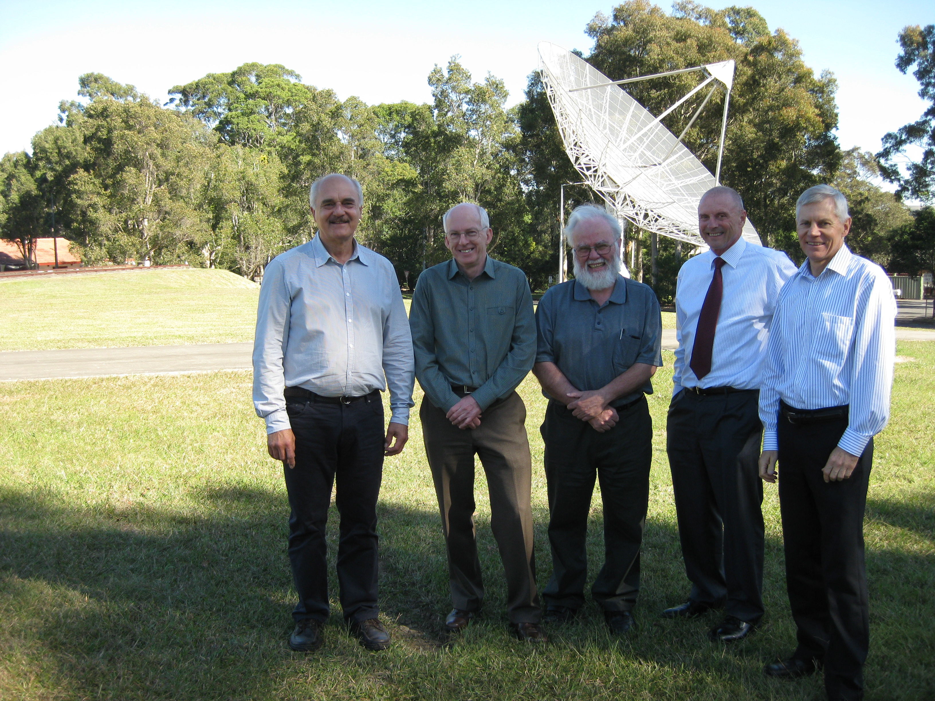 CSIRO's WLAN team standing on the lawn in front of small radio telescope.