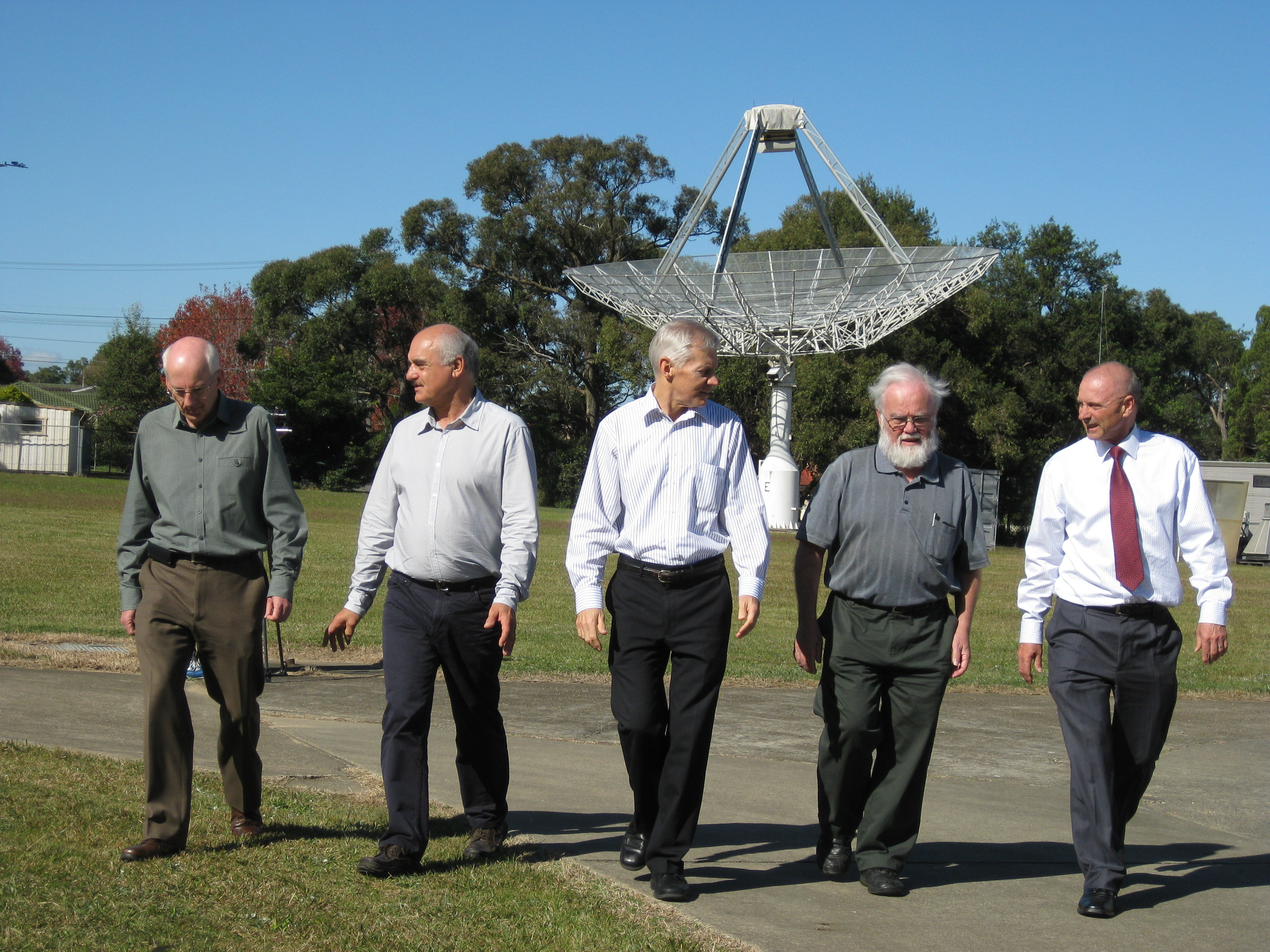 CSIRO's WLAN team in May 2012 walking together in front of a small radio telescope.
