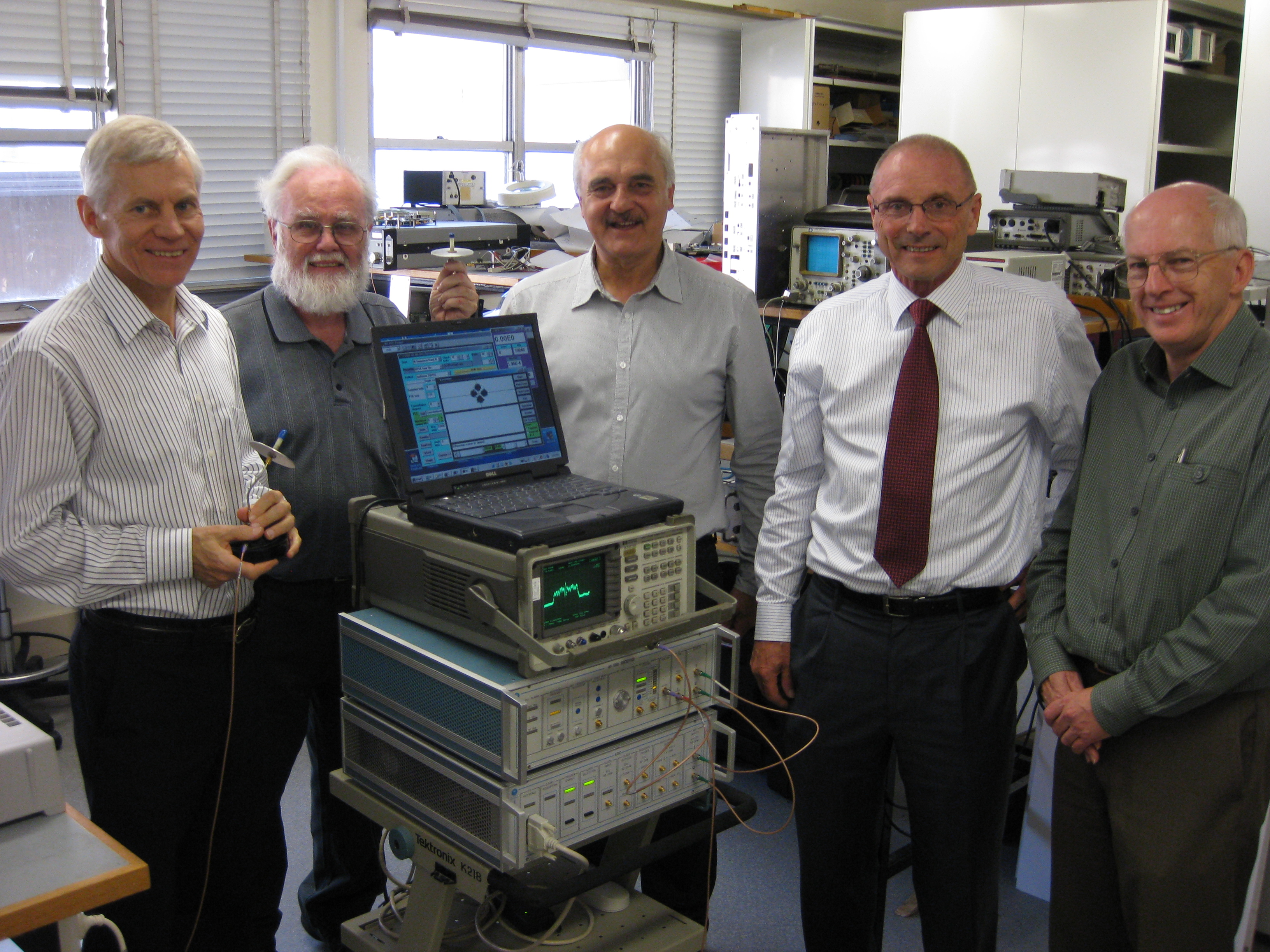 CSIRO's WLAN team standing in the lab with the WLAN testbed.