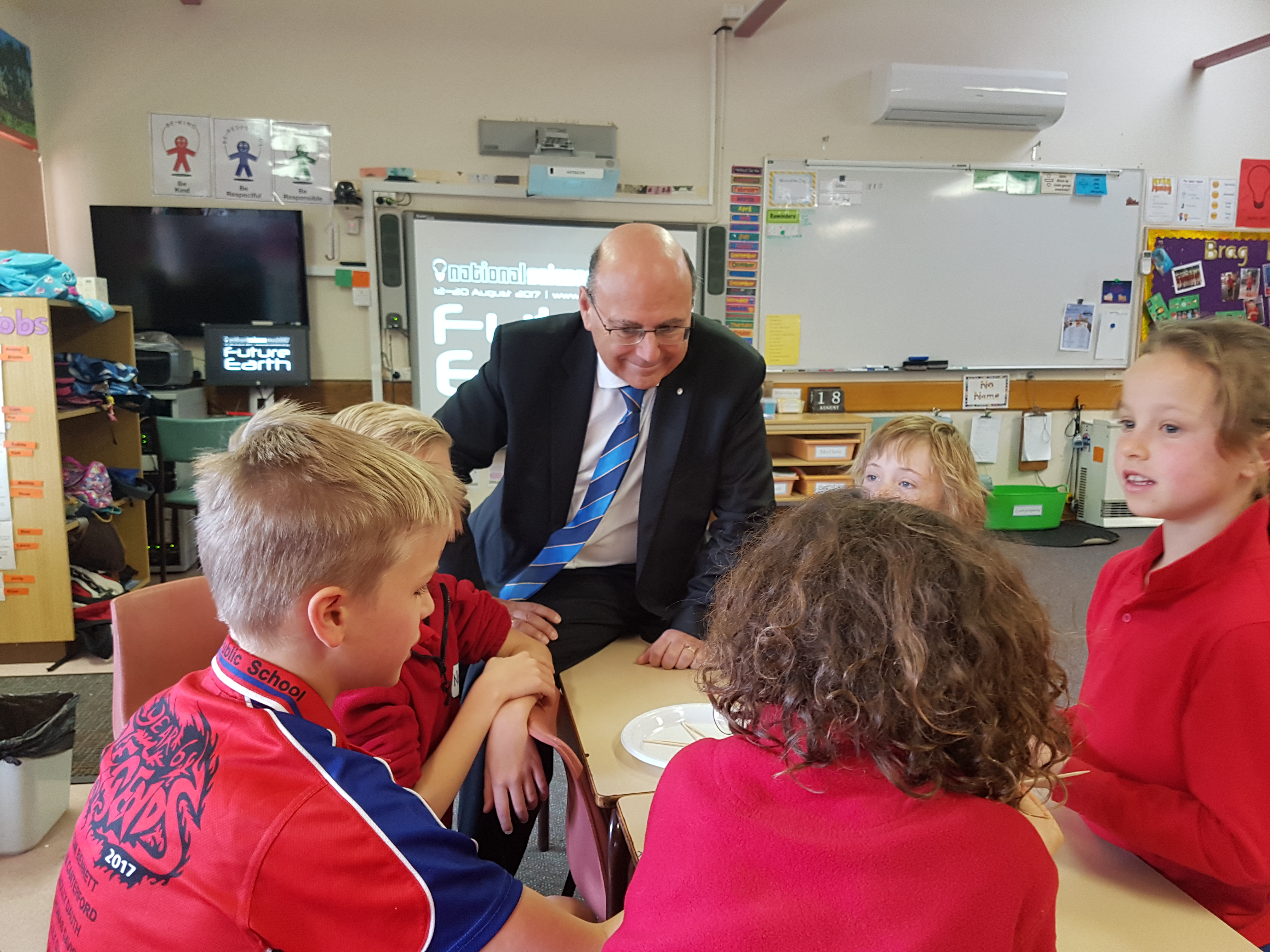 Senator the Hon Arthur Sinodinos AO sitting at a table talking to Gundaroo primary students about science during our STEM in Schools event.