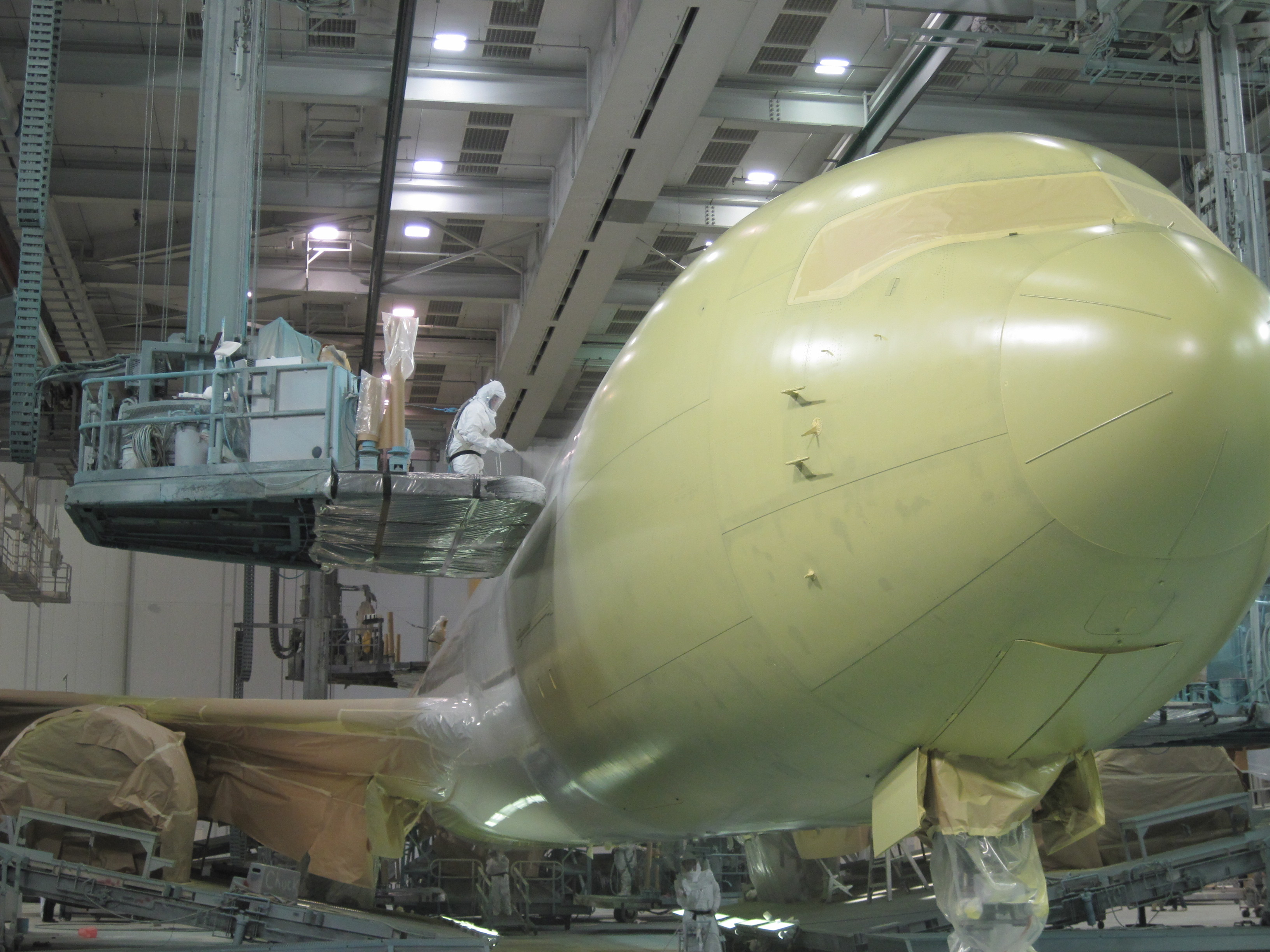 A large commercial aircraft is painted in a hanger.