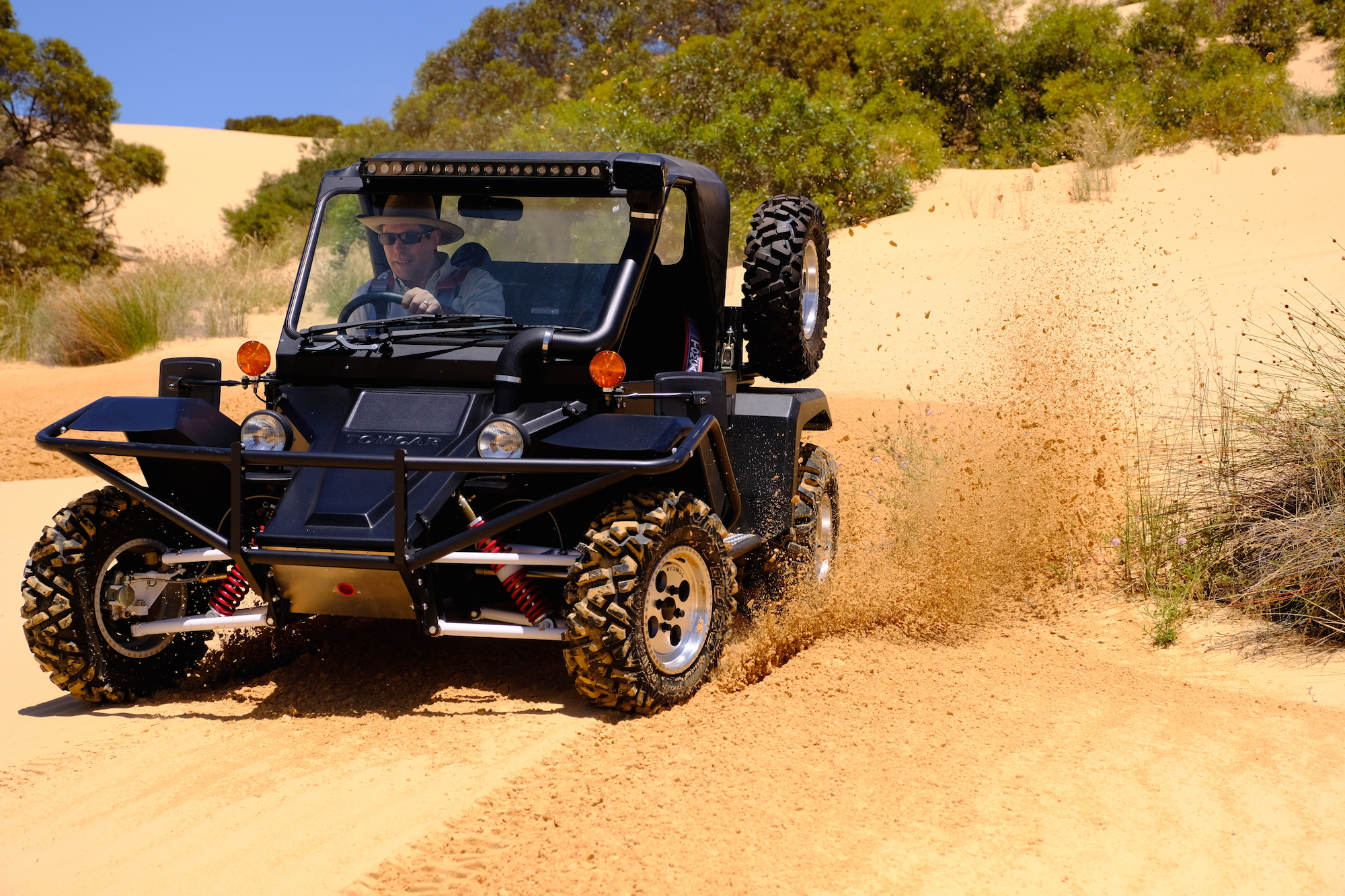 Person driving a Tomcar Australia off-road/off-grid vehicle.
