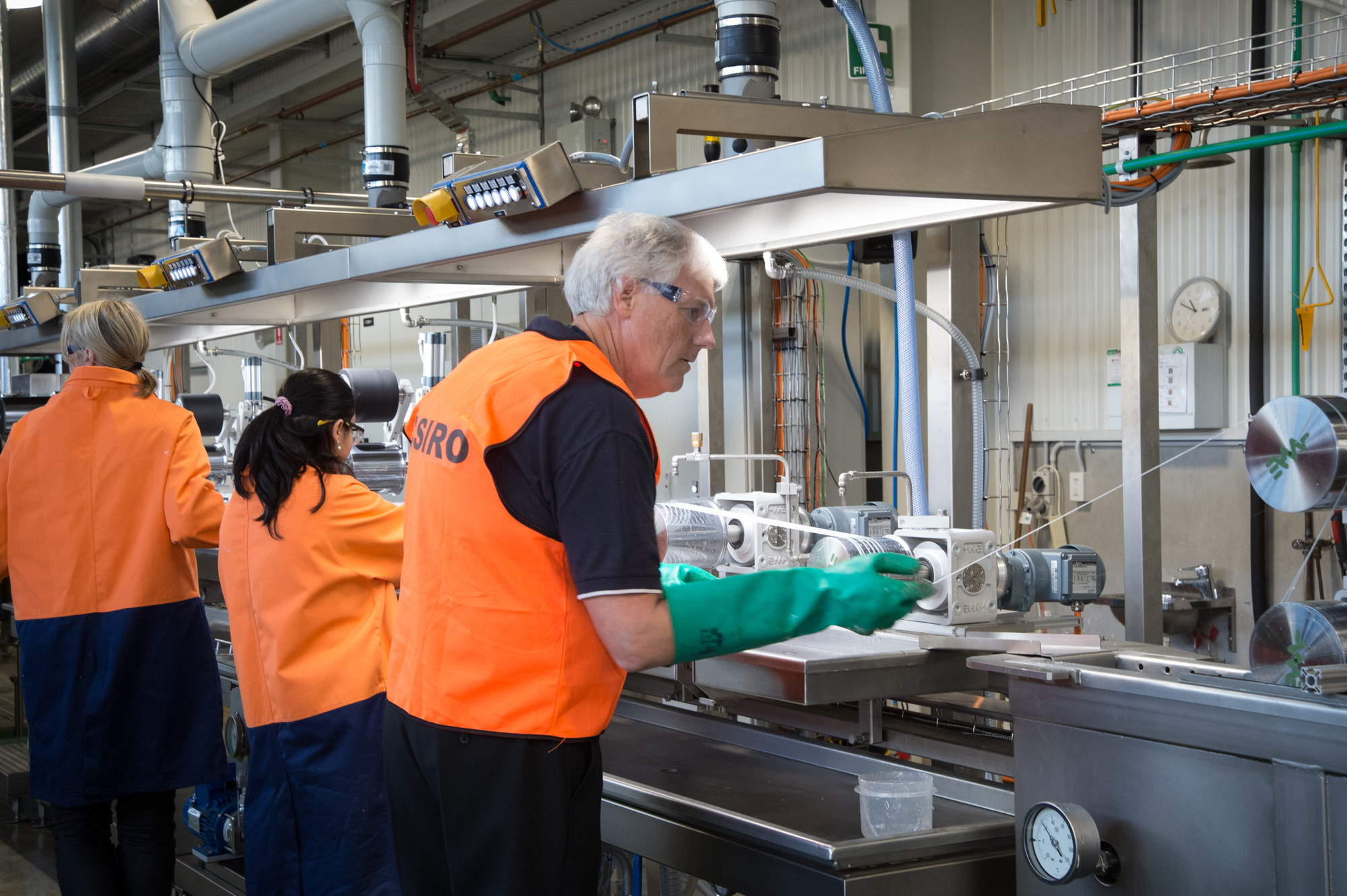 Scientists wearing protective glasses and hi-vis vests working with factory equipment.