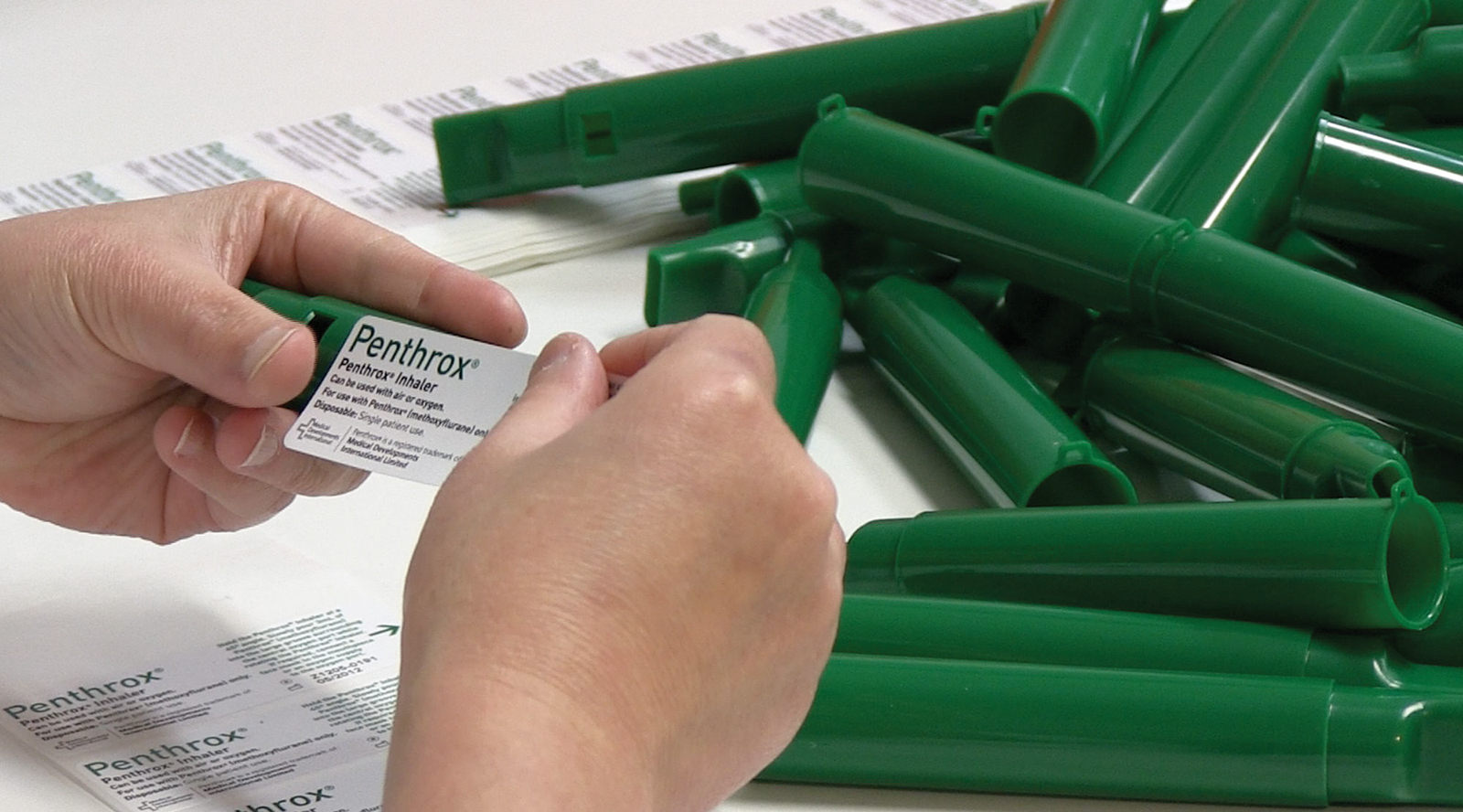 Hands holding Penthrox label above inhaler tubes piled on table.