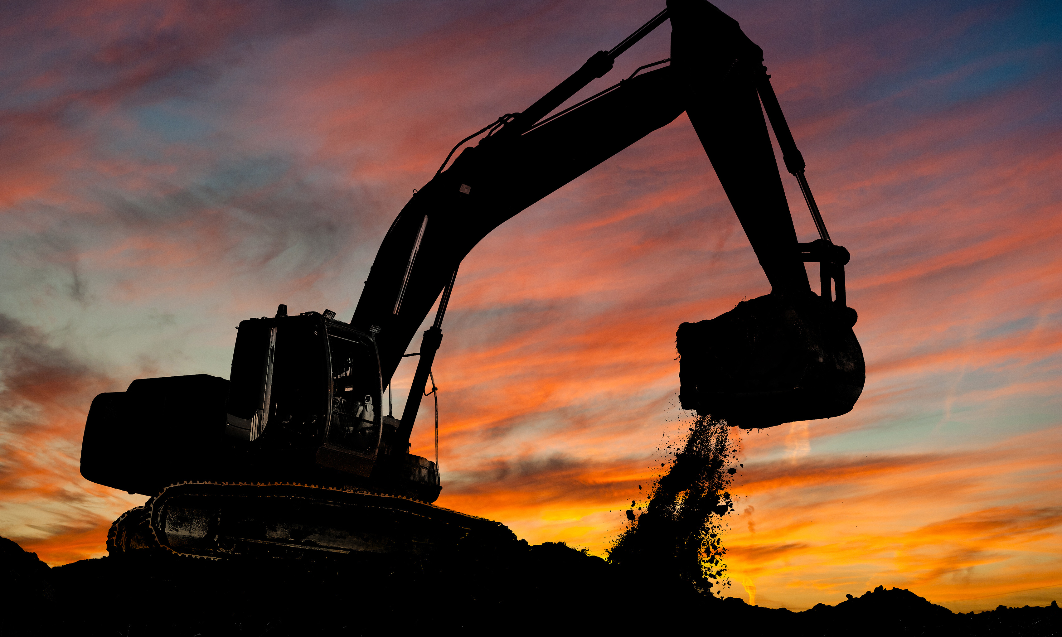 Front-end loader digging earth silhouetted against a sunset sky.