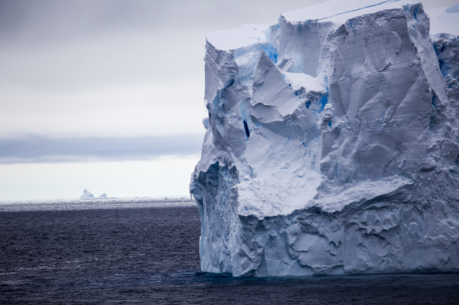 Side view of a large iceberg floating on the ocean.